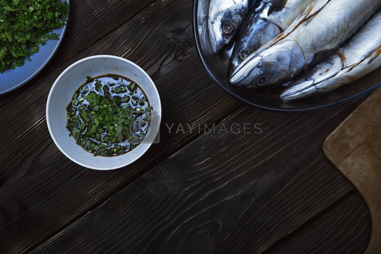 Fish with herbs and vegetables on a wooden table