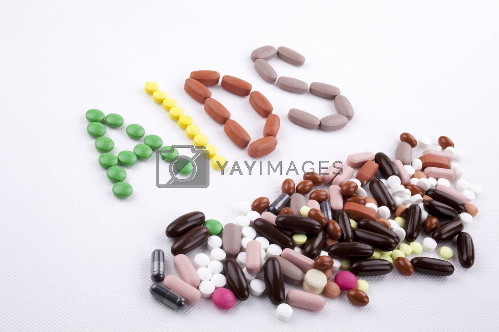 Hand writing text caption inspiration Medical care concept written with pills drugs capsule word Aids On white isolated background with copy space by Artur Szczybylo