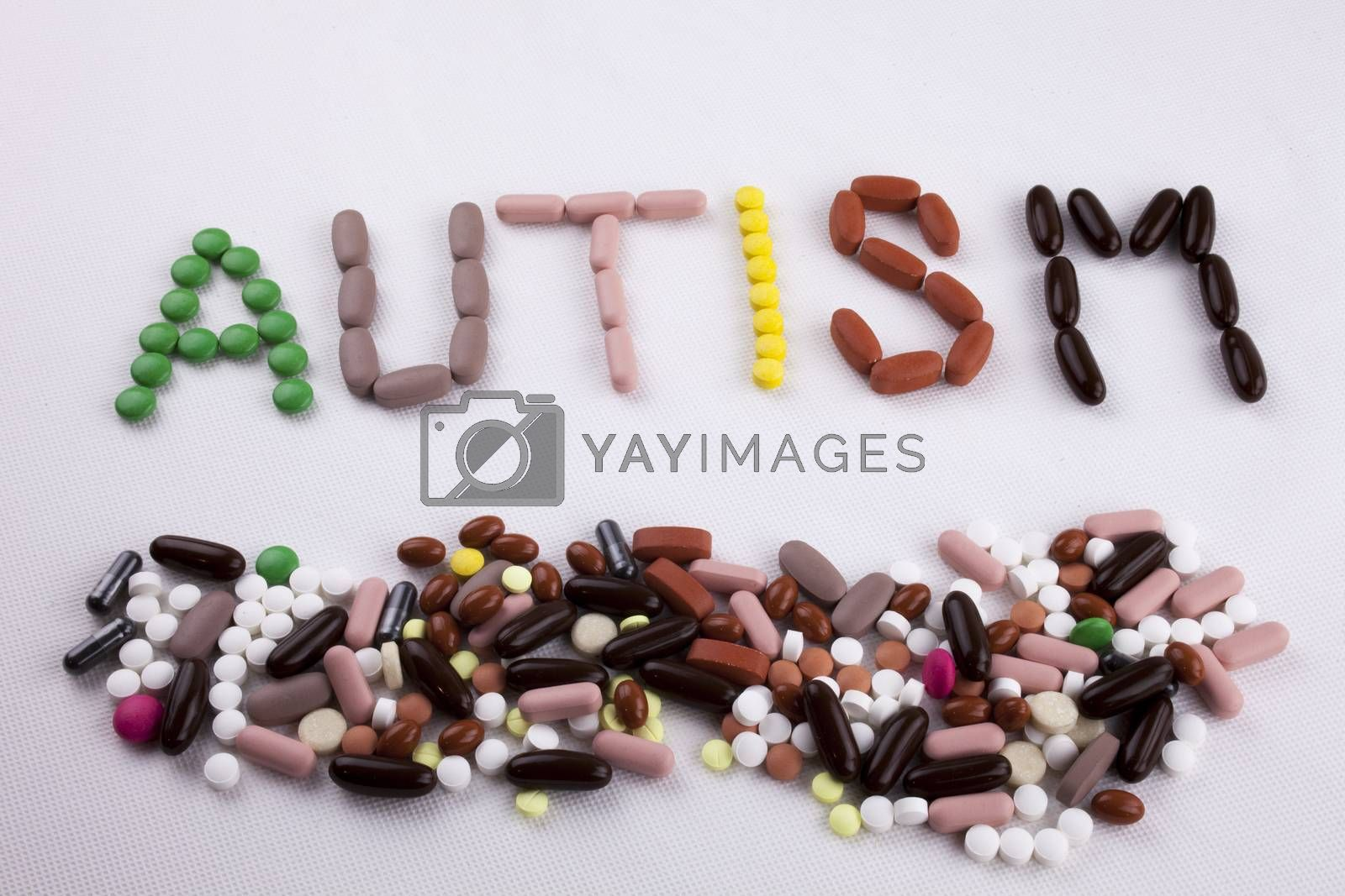 Hand writing text caption inspiration Medical care concept written with pills drugs capsule word AUTISM On white isolated background with copy space by Artur Szczybylo