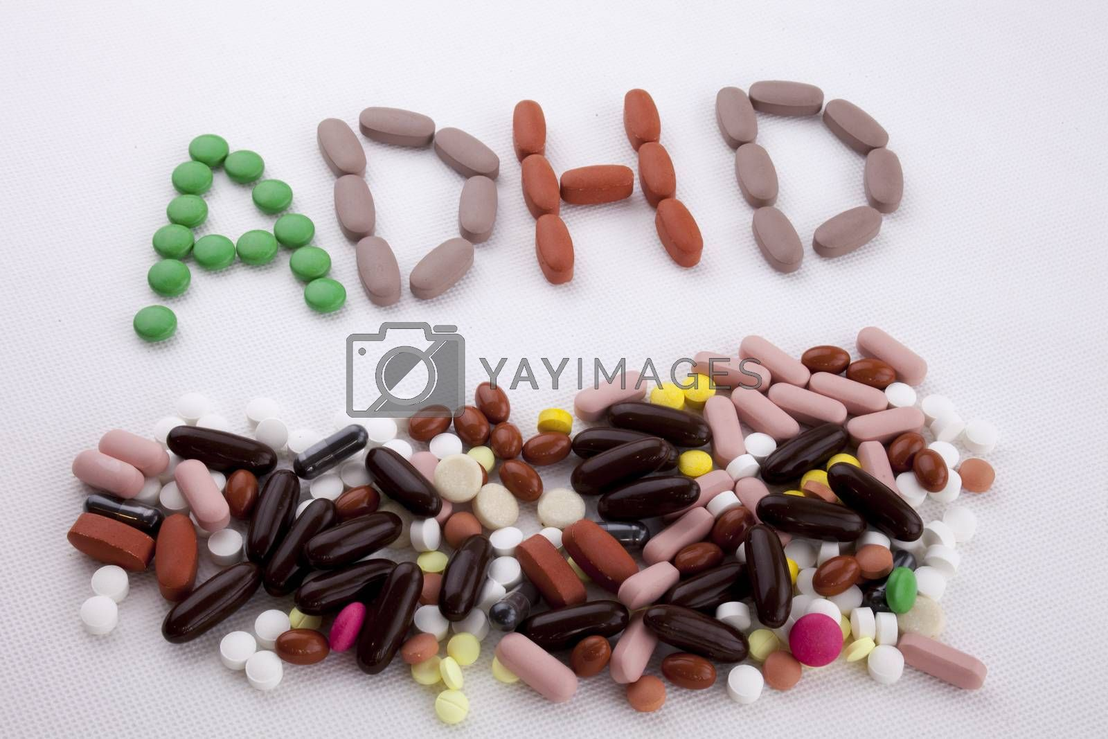 Hand writing text caption inspiration Medical care concept written with pills drugs capsule word ADHD Attention Deficit Hyperactivity Disorder On white isolated background with copy space by Artur Szczybylo