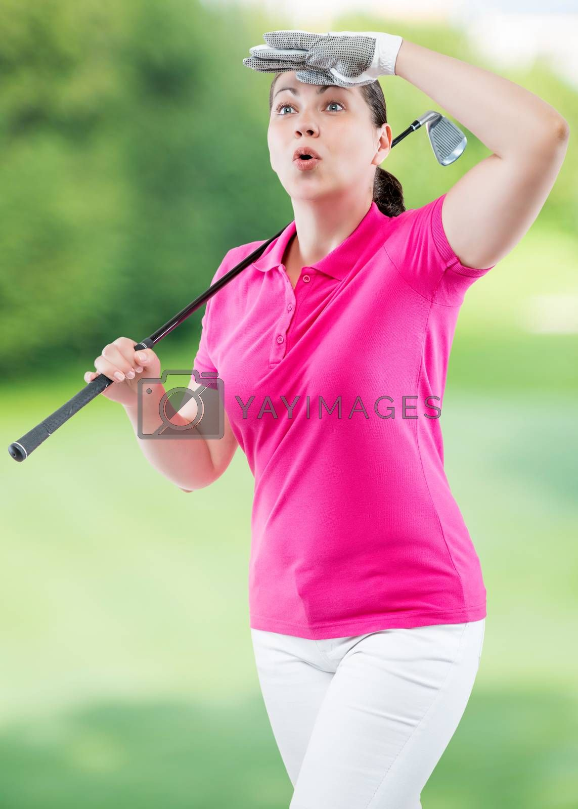 athlete woman watching the ball flight path of golf on a backgro by Labunskiy K.