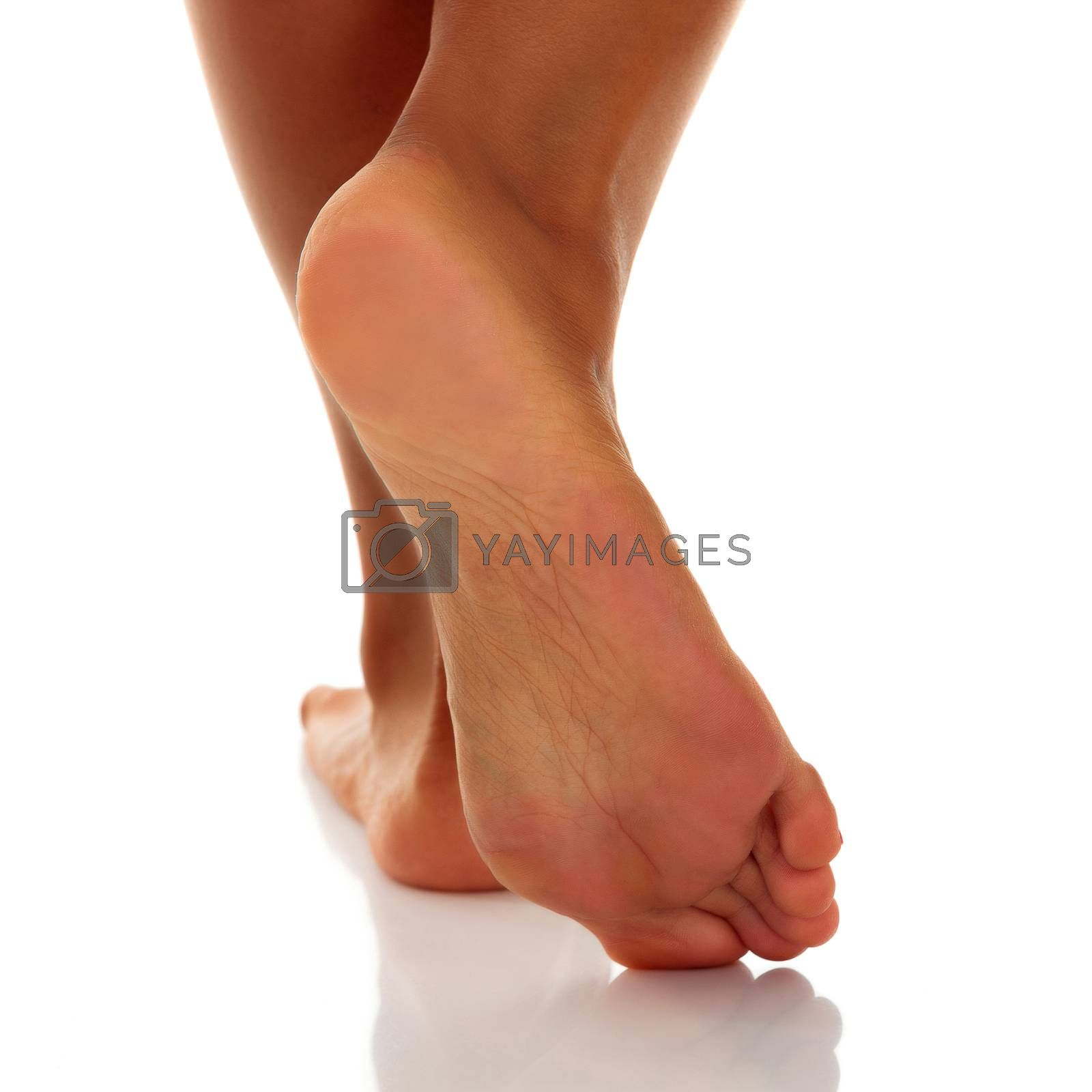 Closeup shot of tanned female feet, isolated on white background