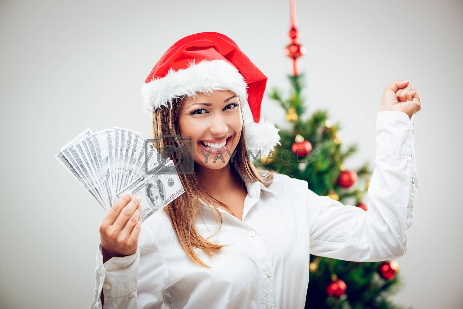 Successful businesswoman wearing santa hat and holding stack of a money.