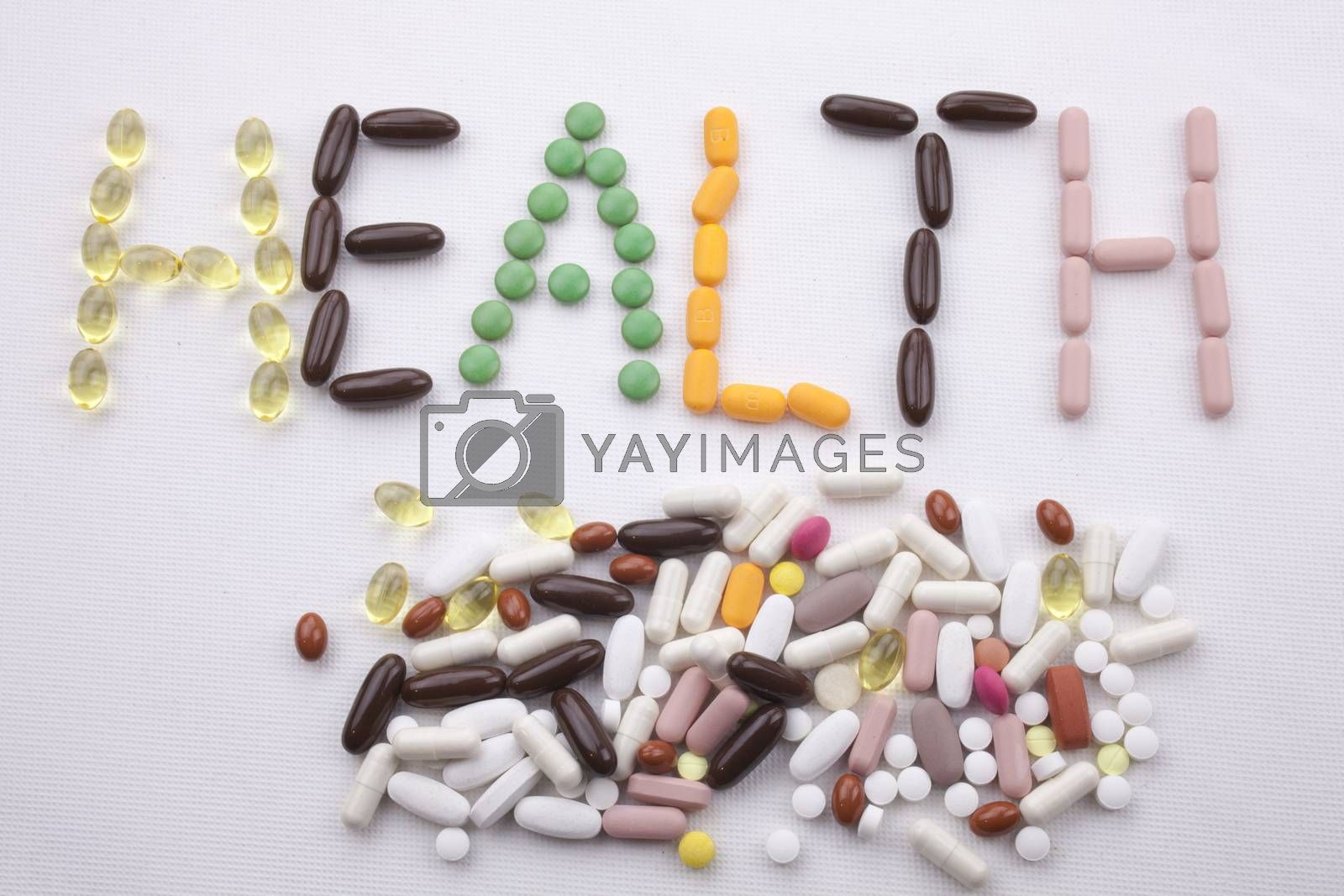 Conceptual Hand writing text caption inspiration Medical care Health concept written with pills drugs capsule word HEALTH season On white isolated background with space