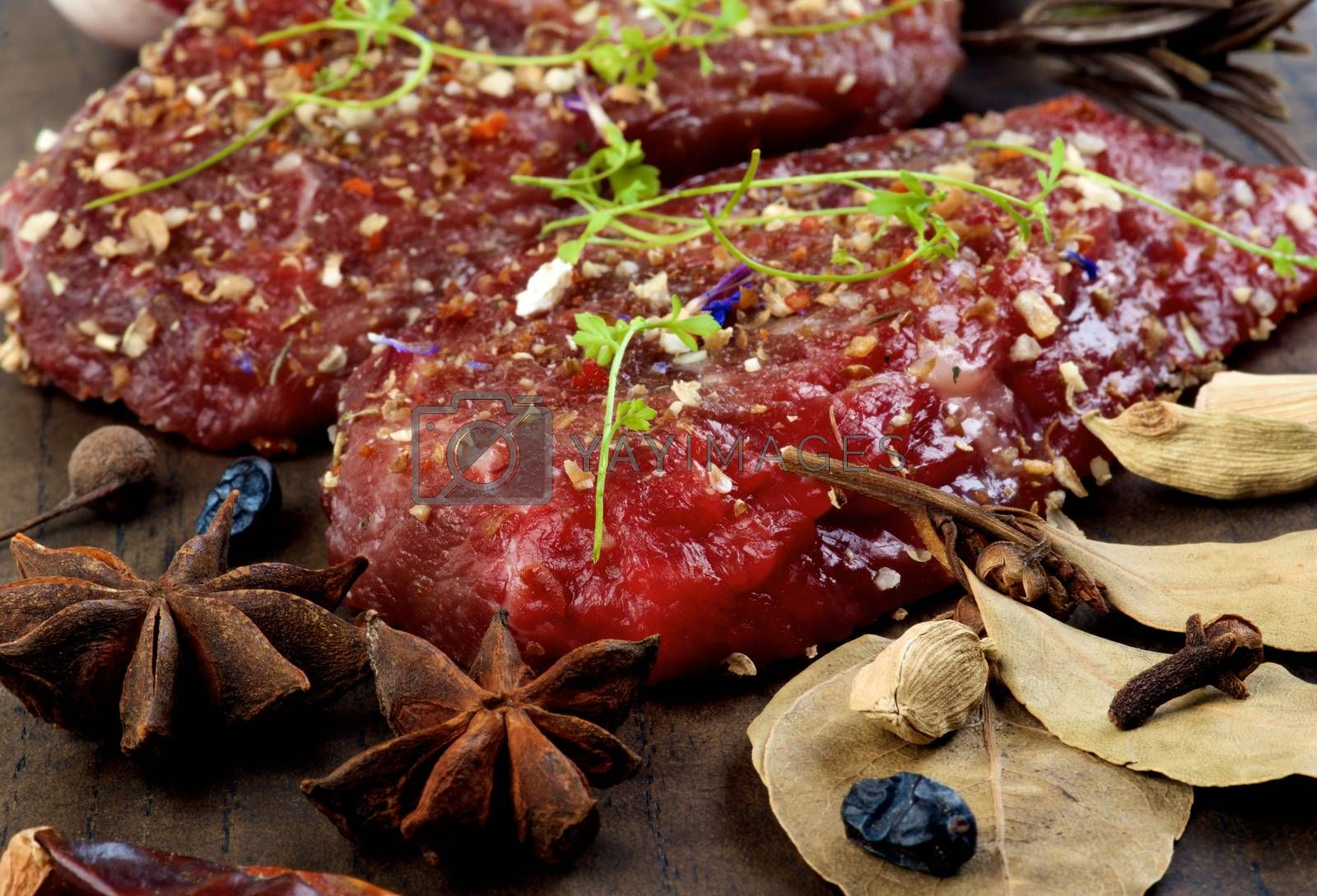 Two Marinated Raw Boneless Beef Steaks with Herbs and Spices, Garlic and Chili Pepper closeup on Wooden Cutting Board. Focus on Foreground