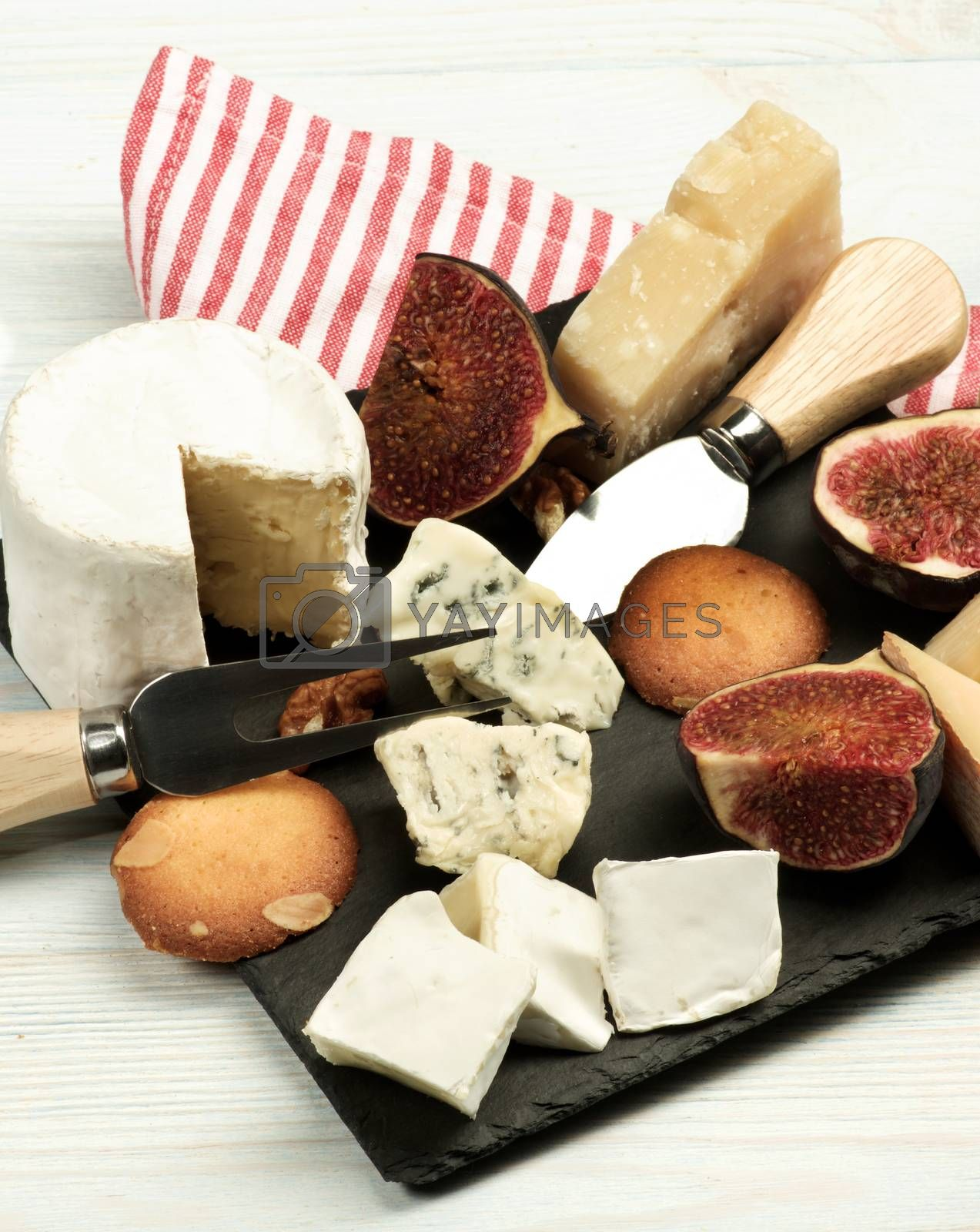 Arrangement of Gourmet Cheese with Brie, Parmesan, Roquefort and Camembert and Figs with Biscuits on Slate Plate closeup on Wooden background