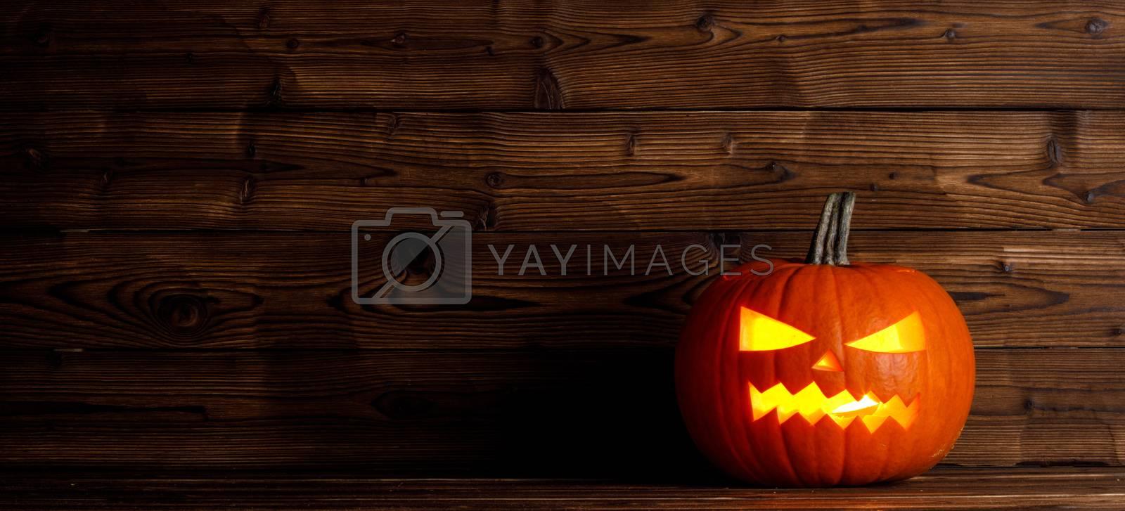 Glowing Halloween pumpkin head jack lantern on wooden background