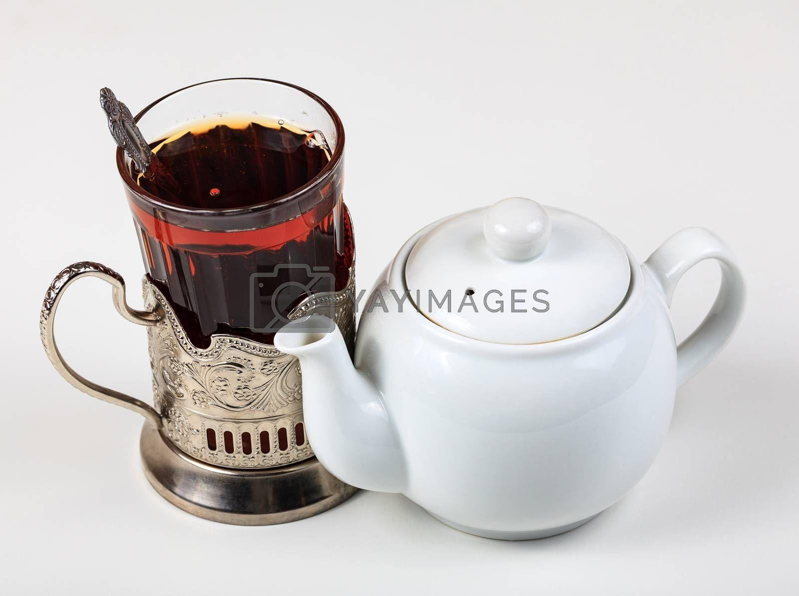 Closeup shot of teapot and glass on white background