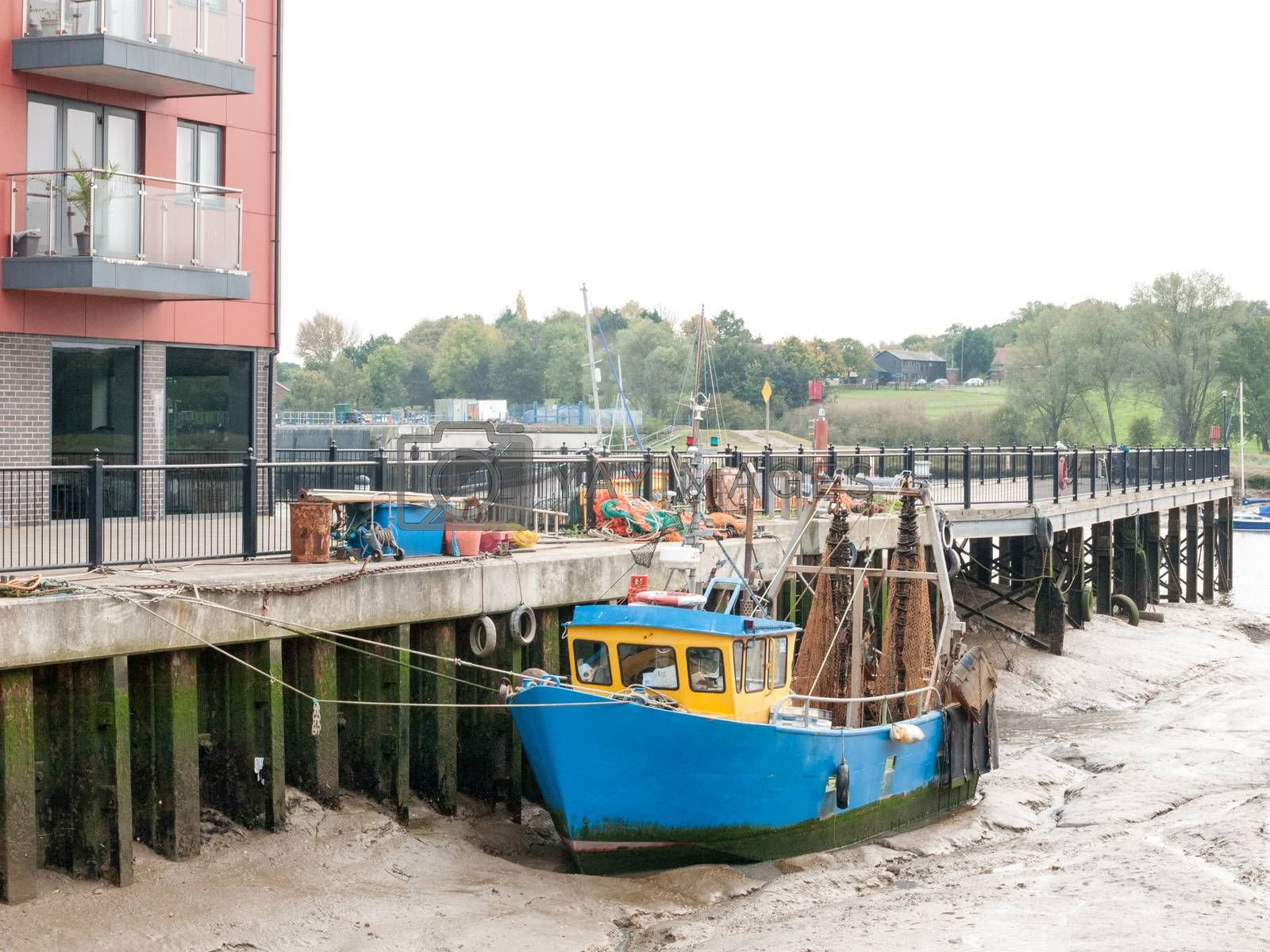 blue fishing boat parked in pier mud dock; essex; england; uk