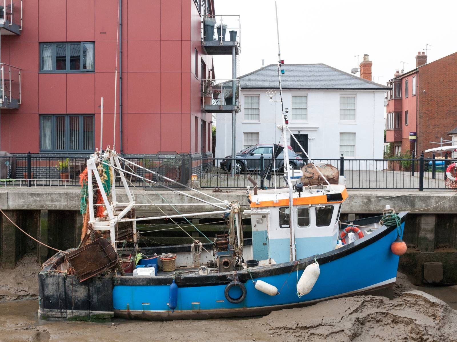 blue fishing boat parked in pier mud dock from side view; essex; england; uk