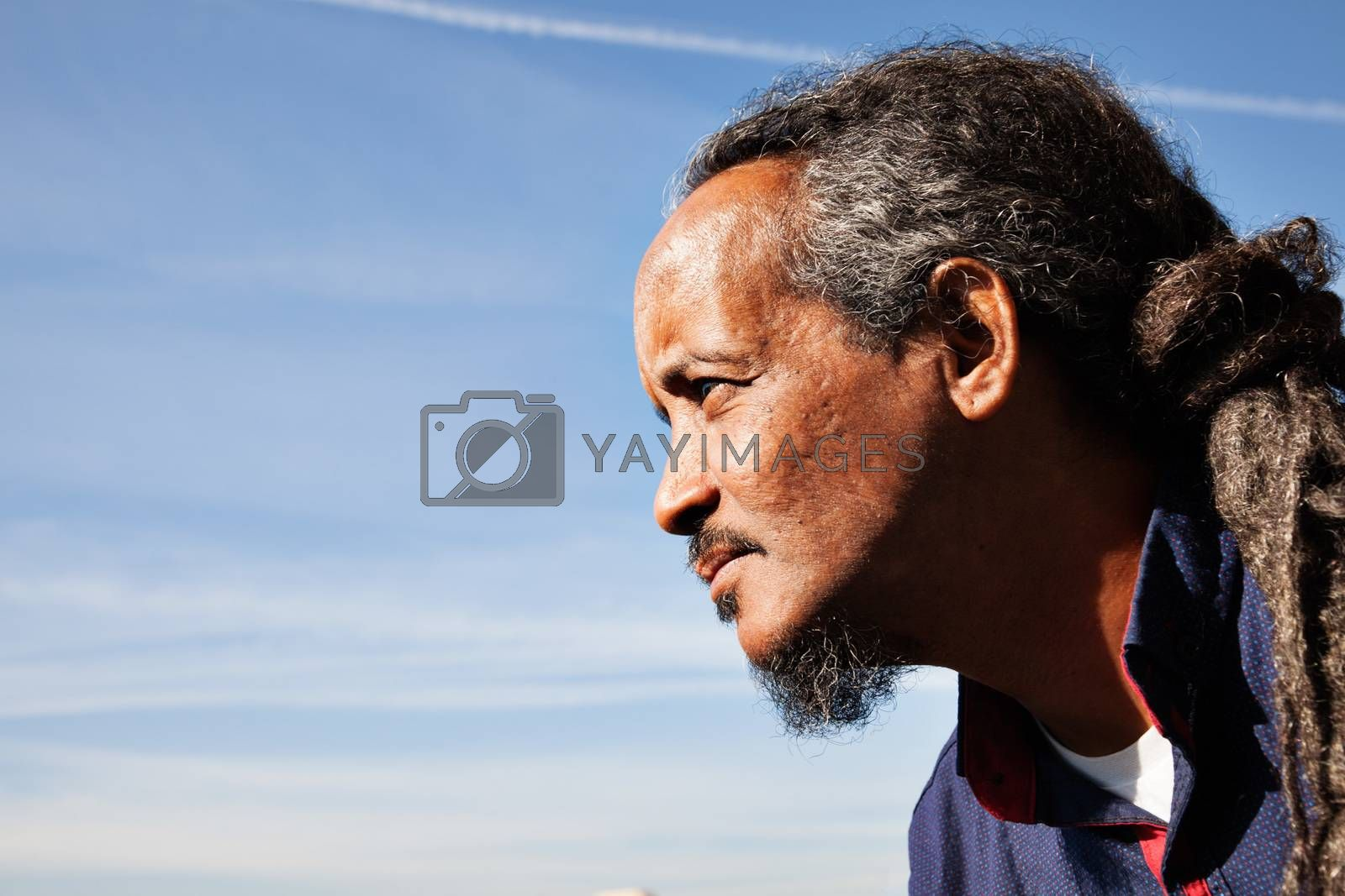 A portrait of a black rastafarian man over a blue sky with some clouds.