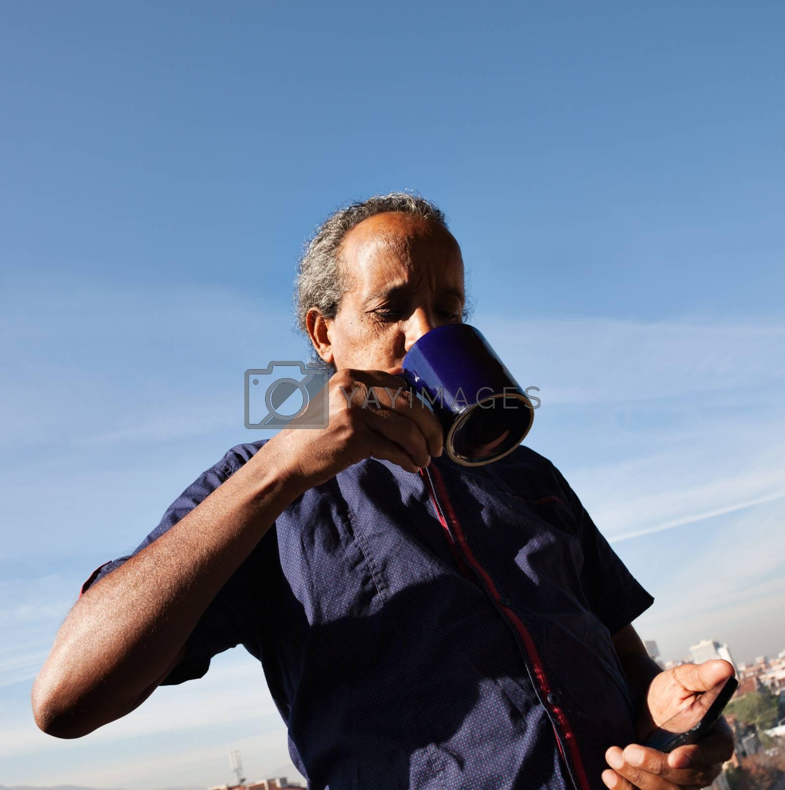 Rasta black man drinking cofee or tea, holding phone, blue sky behind.