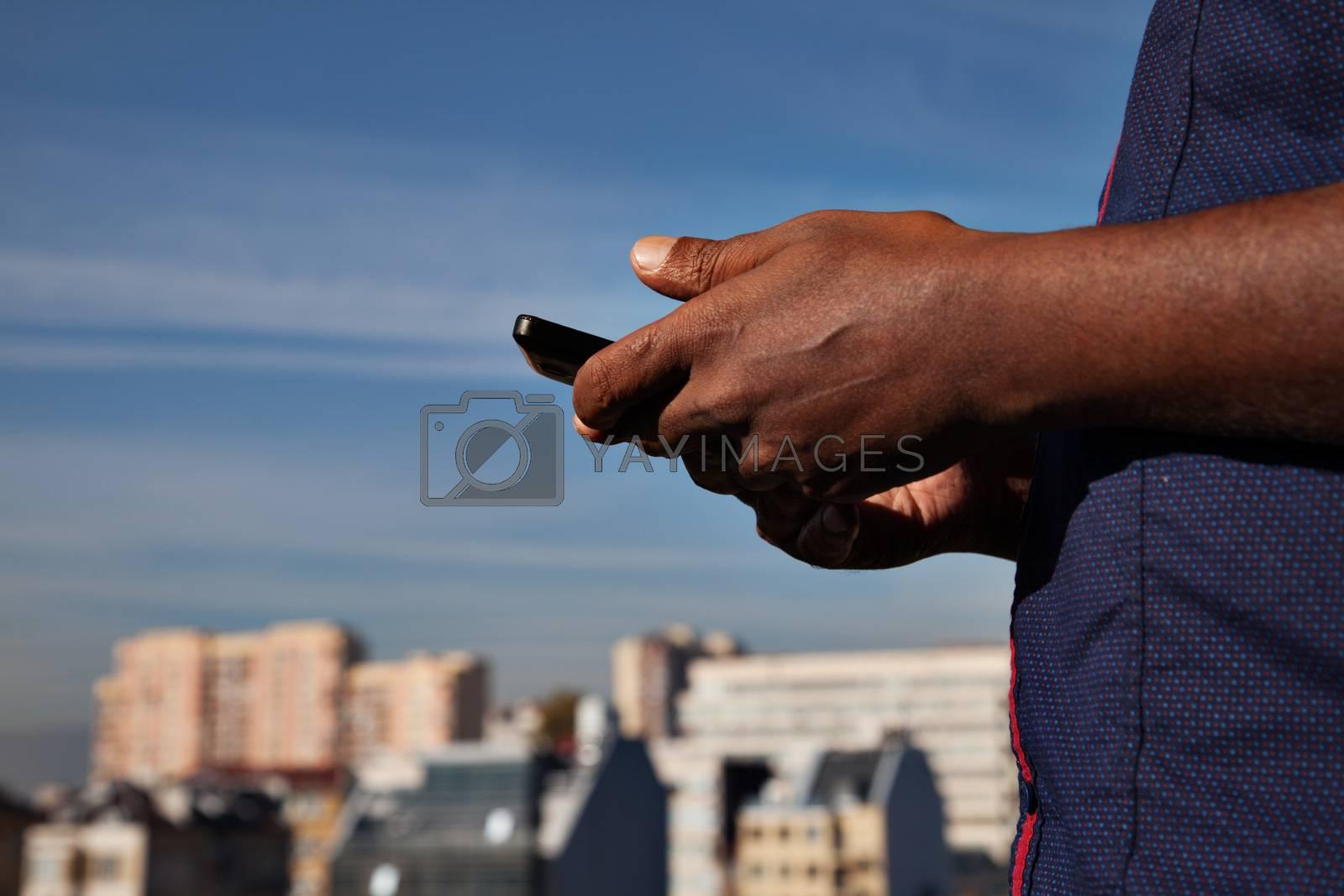black man's hands holding phone above a cityline