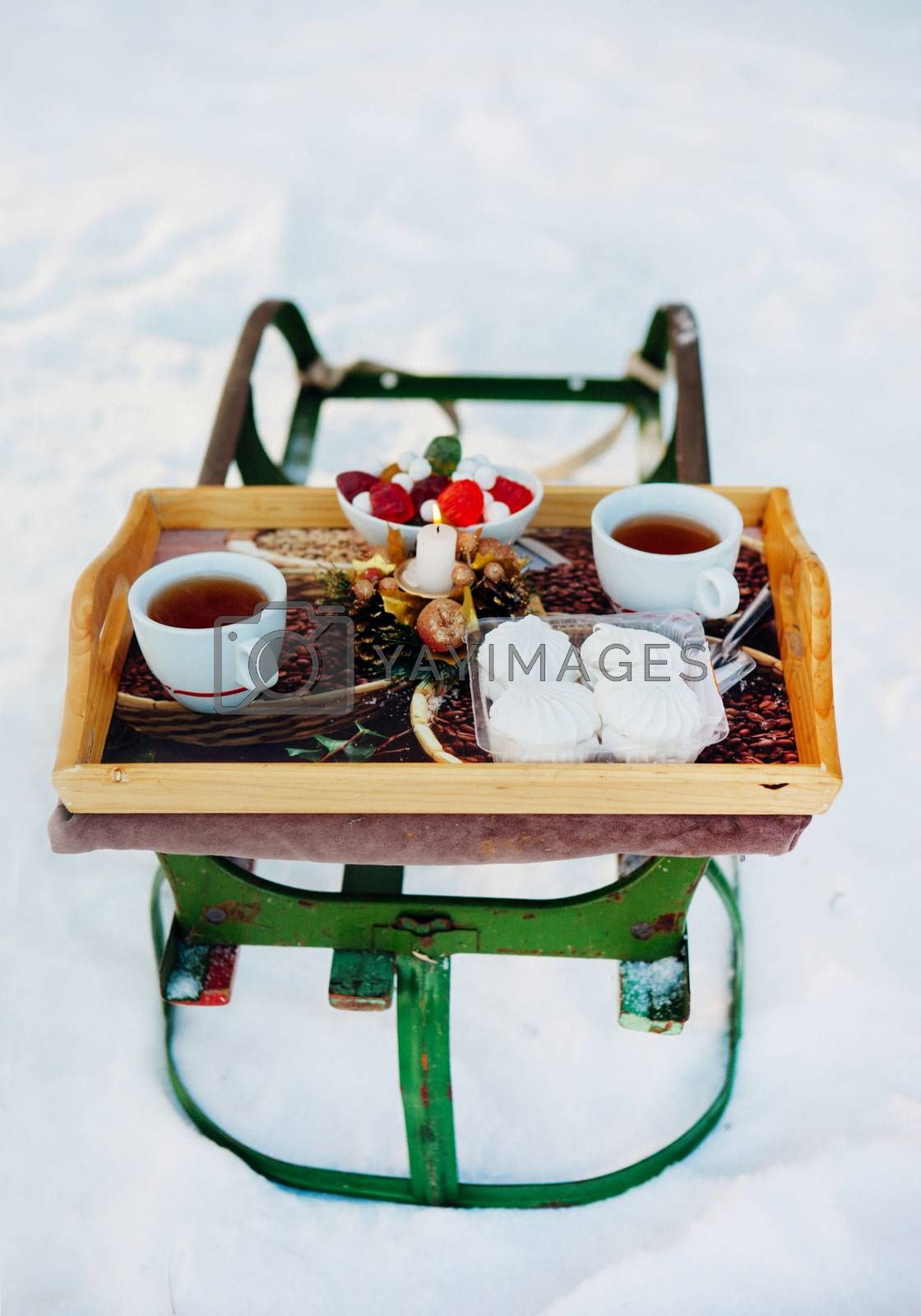 Romantic breakfast in the snow. Winter Vintage Sledge. Coffee, marshmallows, and other sweets in a compartment with a burning candle