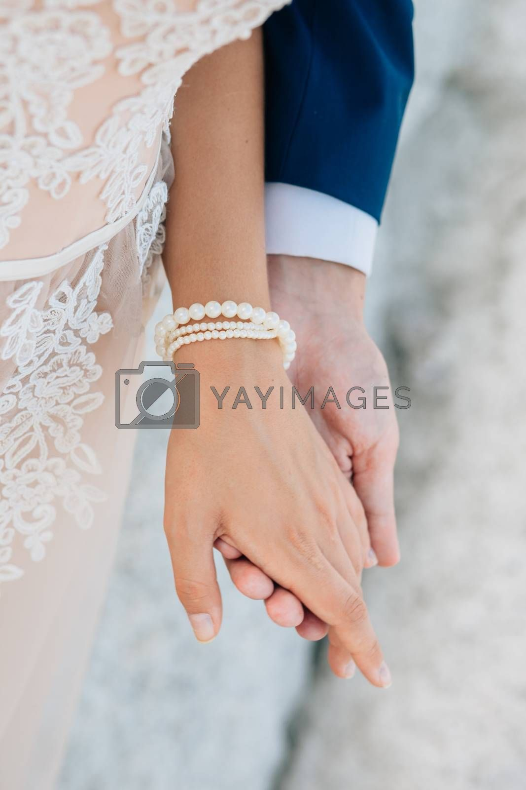 The groom gently holds the bride by the hand, close-up