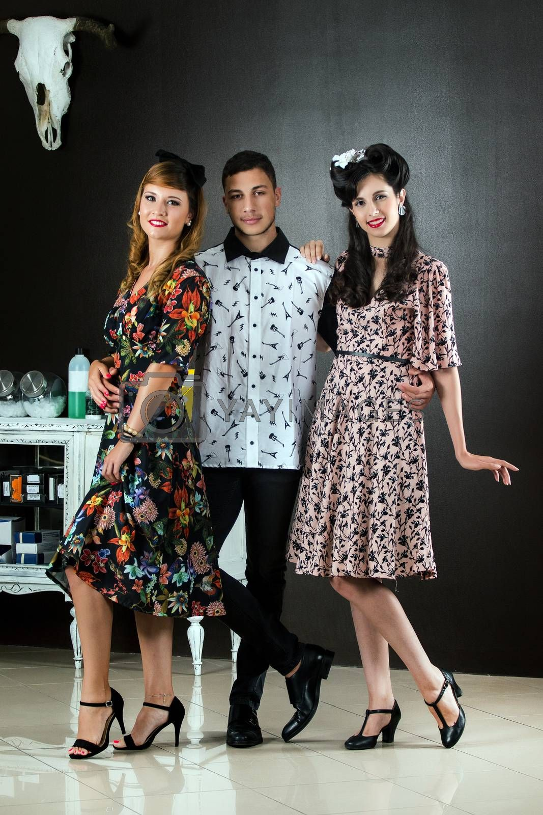 Two woman and a man posing on a vintage style retro clothing.