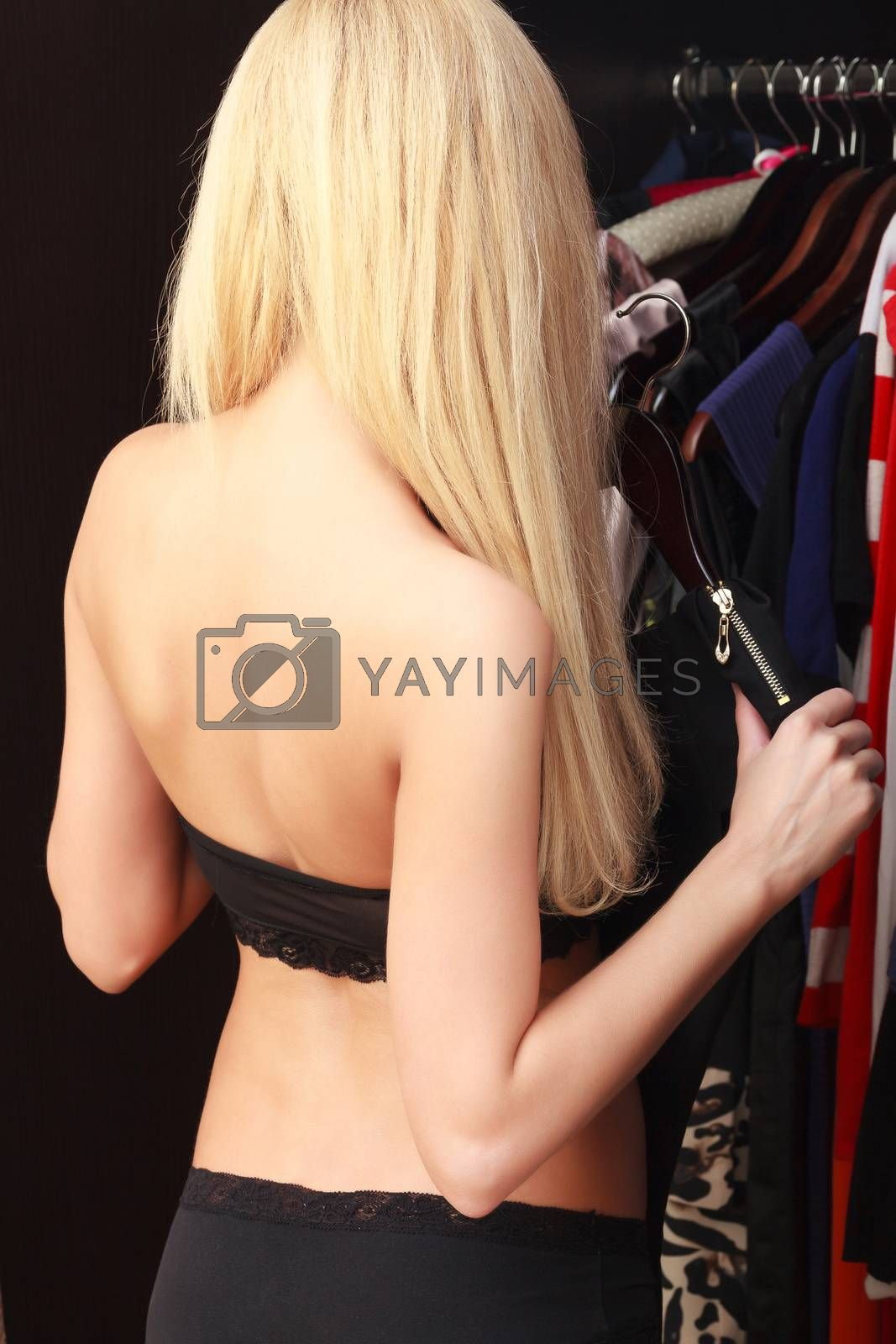 Young woman choose clothes in wardrobe at her place, view from behind
