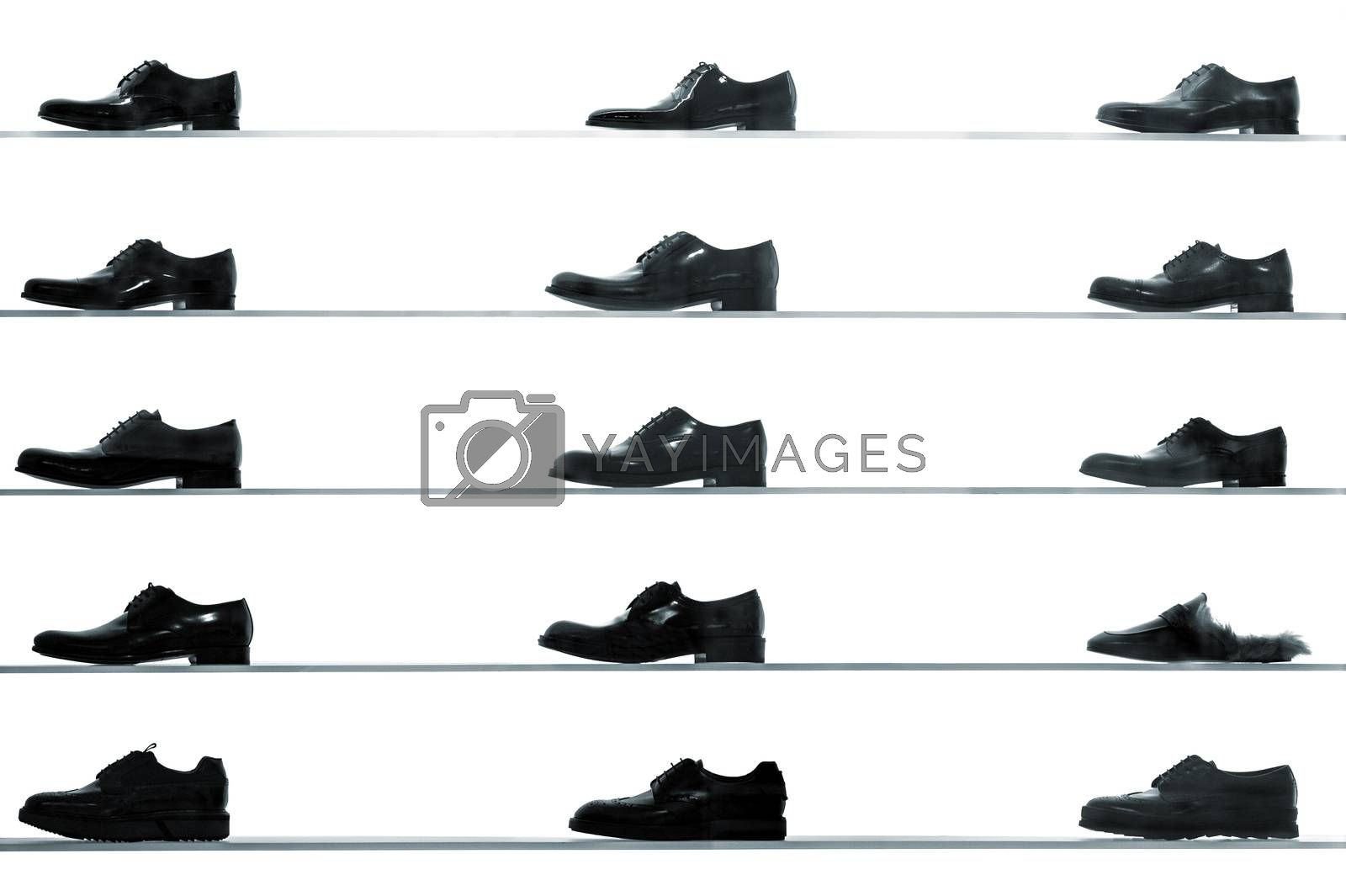 Men classic shoes displayed on shop shelves against back lit white background. High contrast black and white abstract looking picture