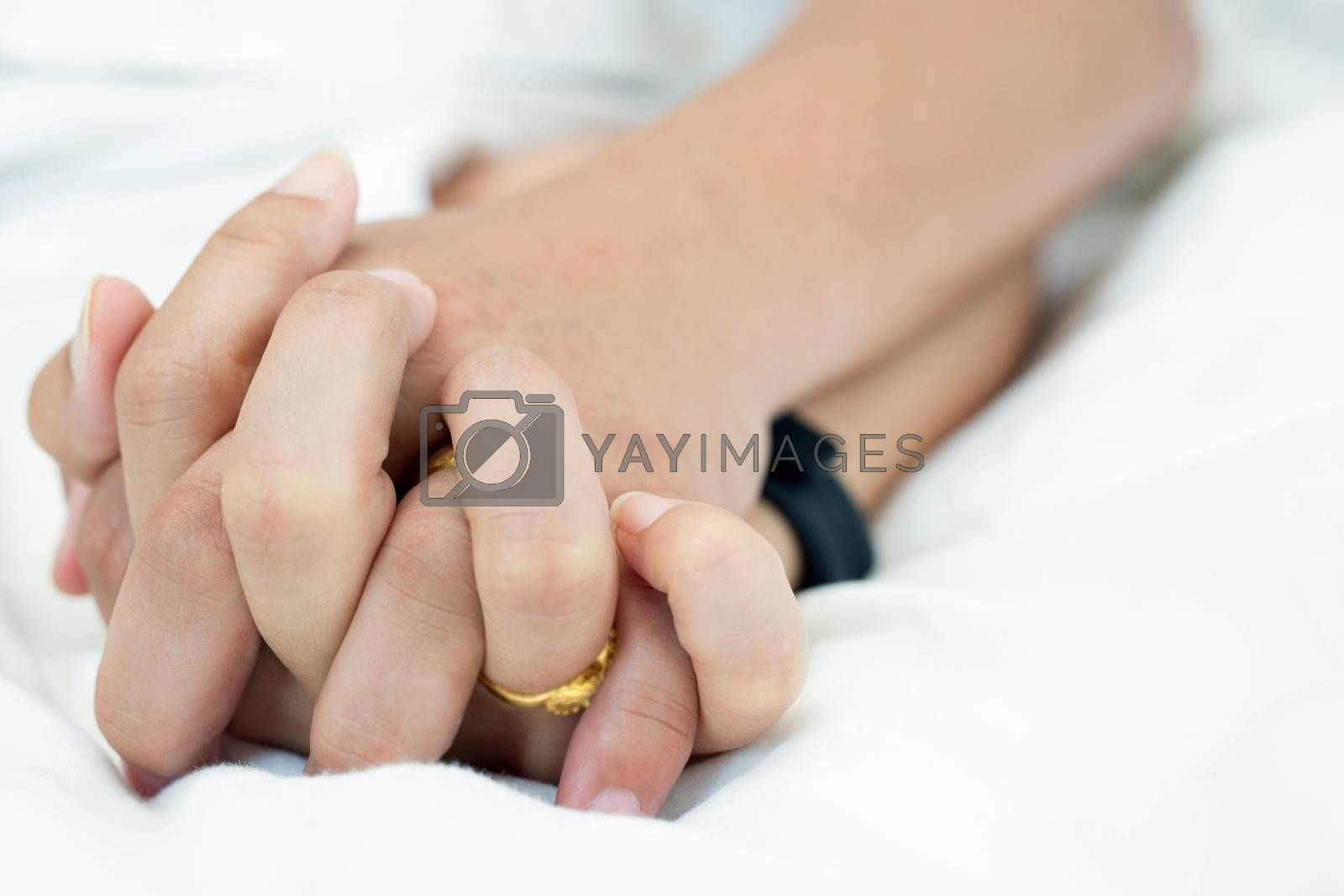 Hands stranglehold of couple lovers on a bed at honeymoon with lust and love. Concept about love, sex and lifestyle.