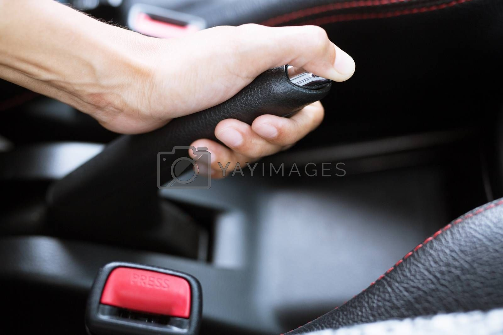 Closeup of young woman pulling handbrake lever in car For safety while parking.
