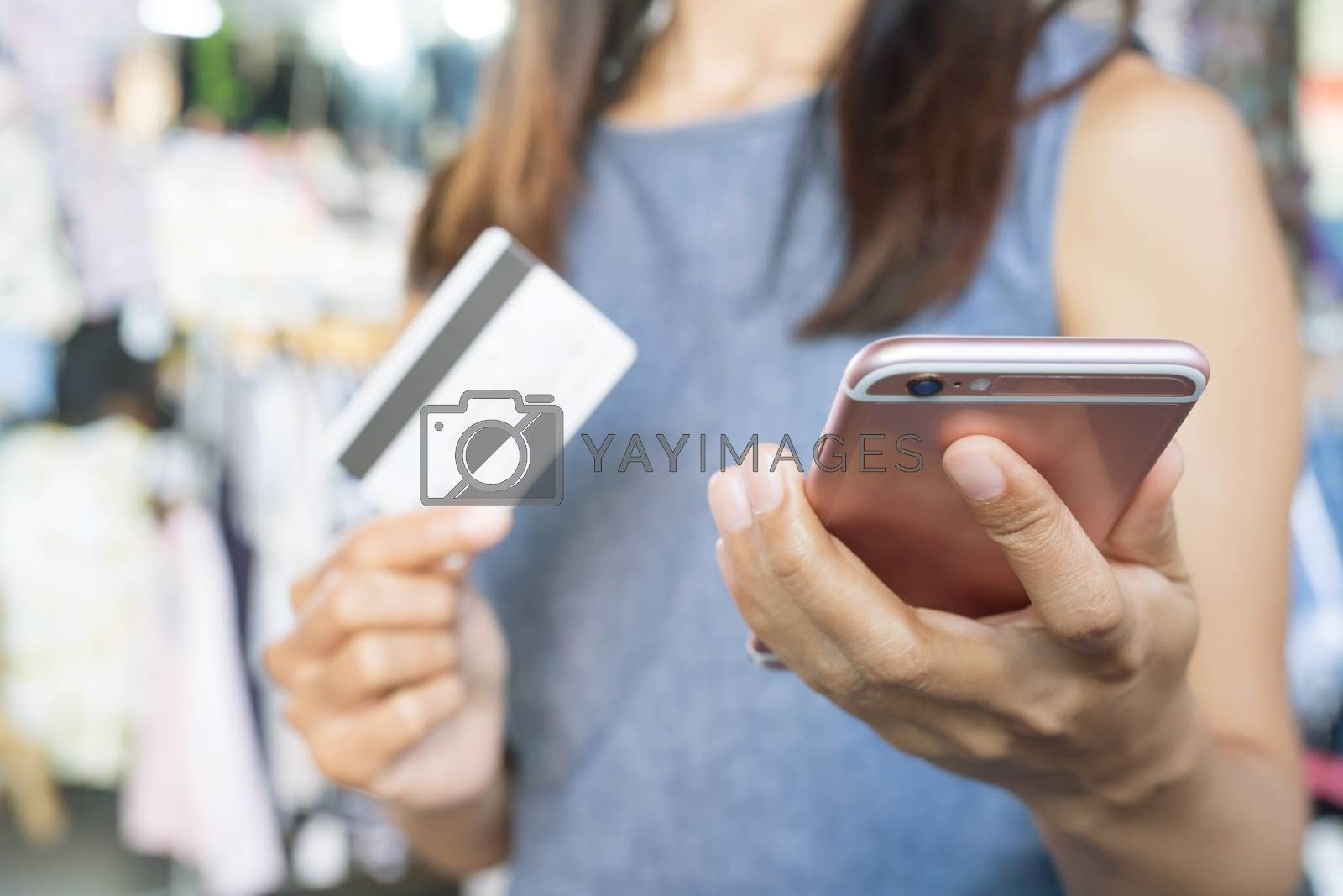 female hands holding credit card and using phone and computer laptop. Online shopping purchase Sell or Payment.