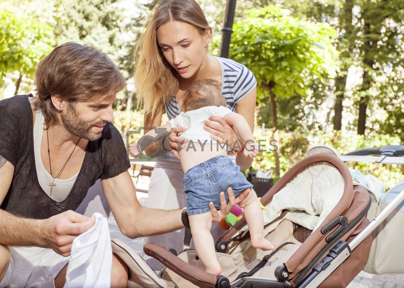 A young mother and a father are taking care of their baby on a sunny summer day.