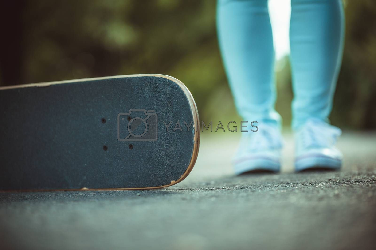 female feet in white sneakers and skateboard close up
