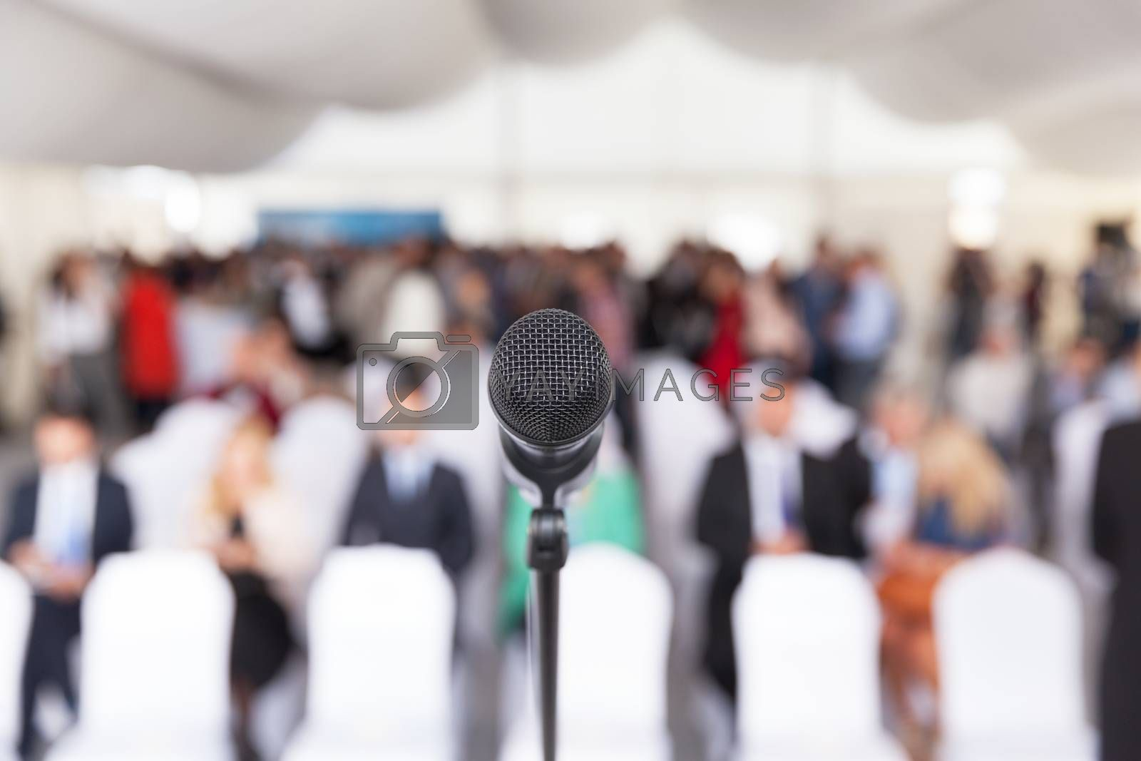Microphone in focus against blurred audience. Participants at the business or professional conference.