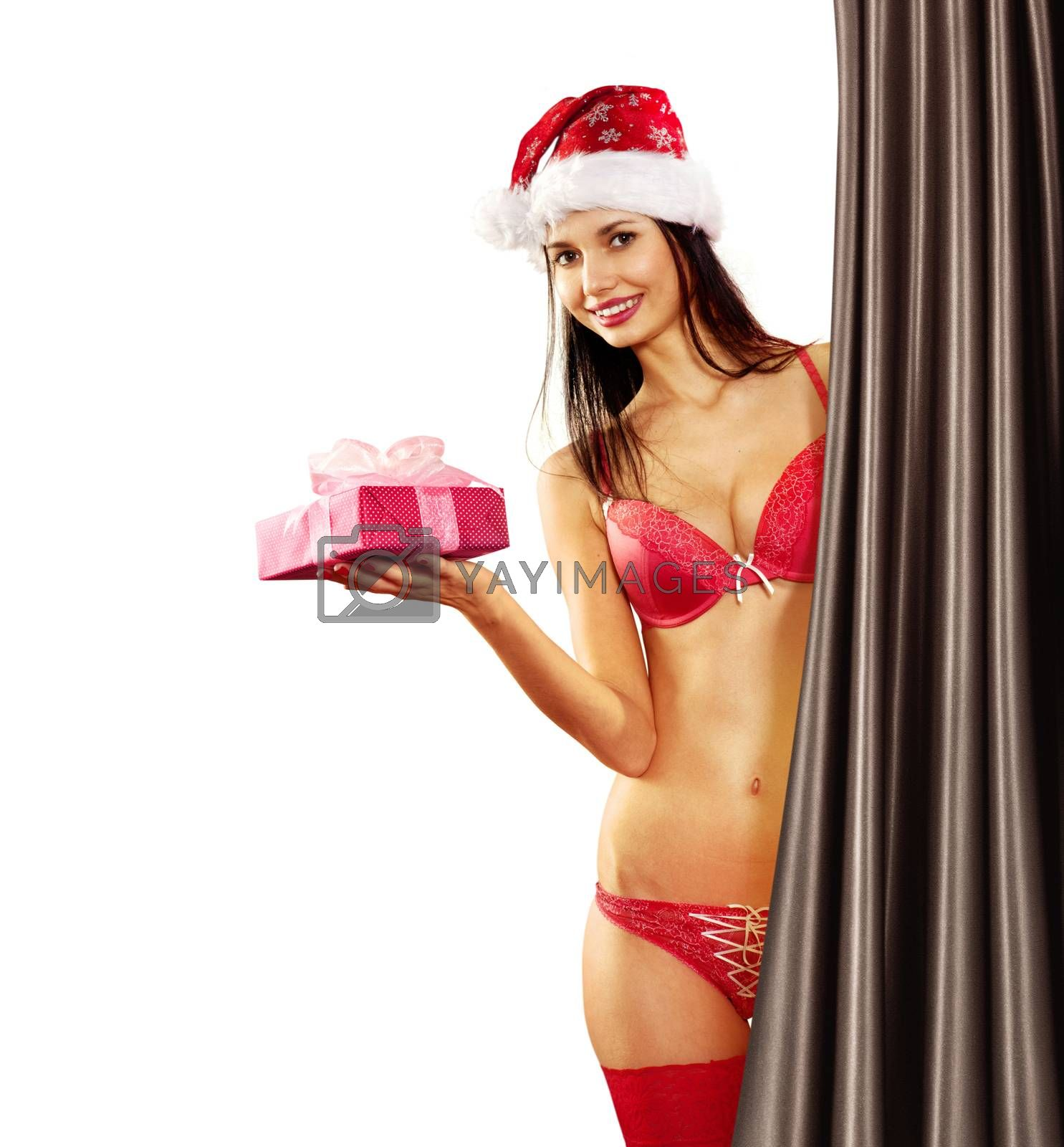 Beautiful and sexy woman with gift wearing santa clause costume hides behind a curtain