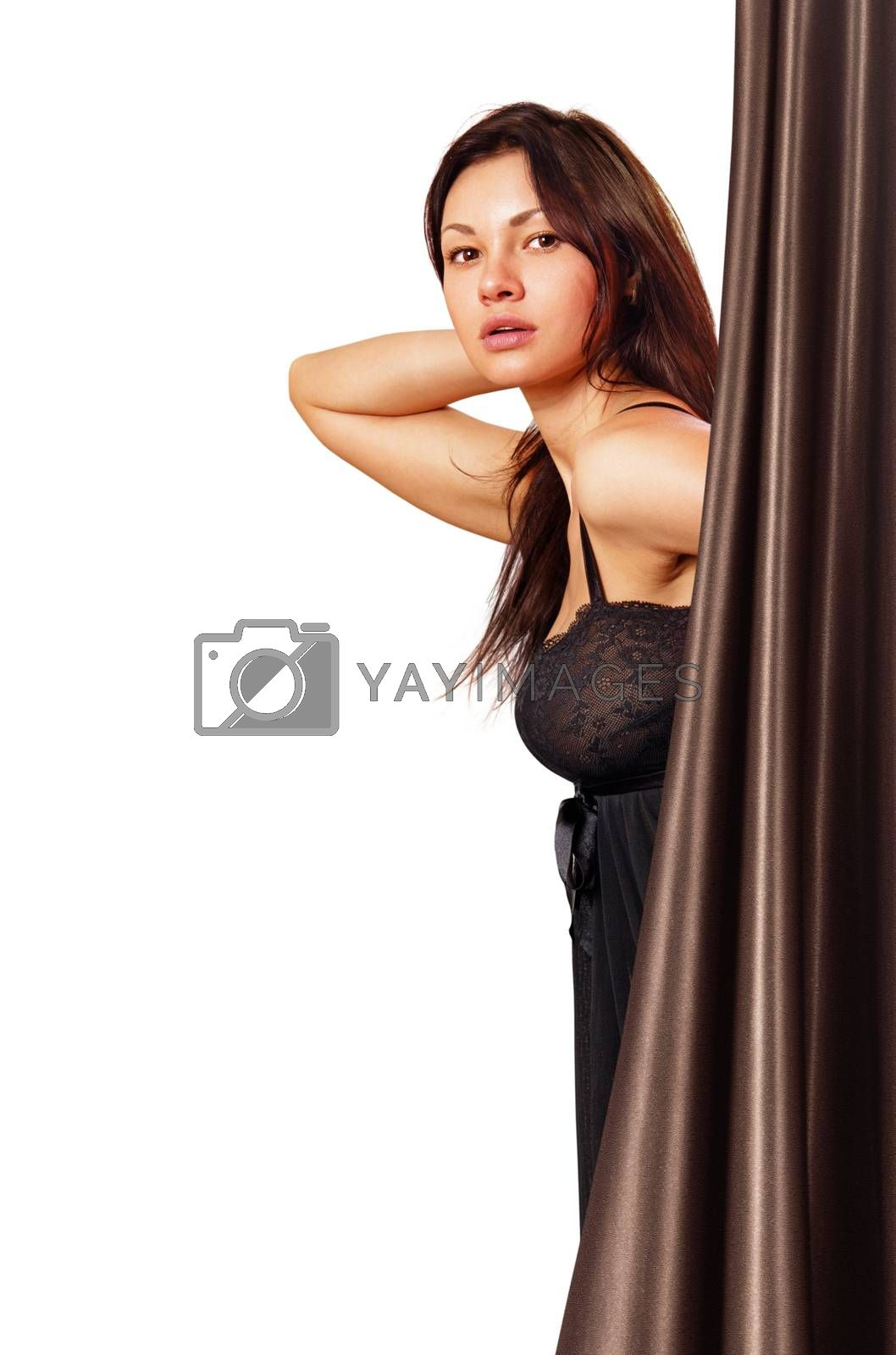 beautiful young woman looks out from curtains