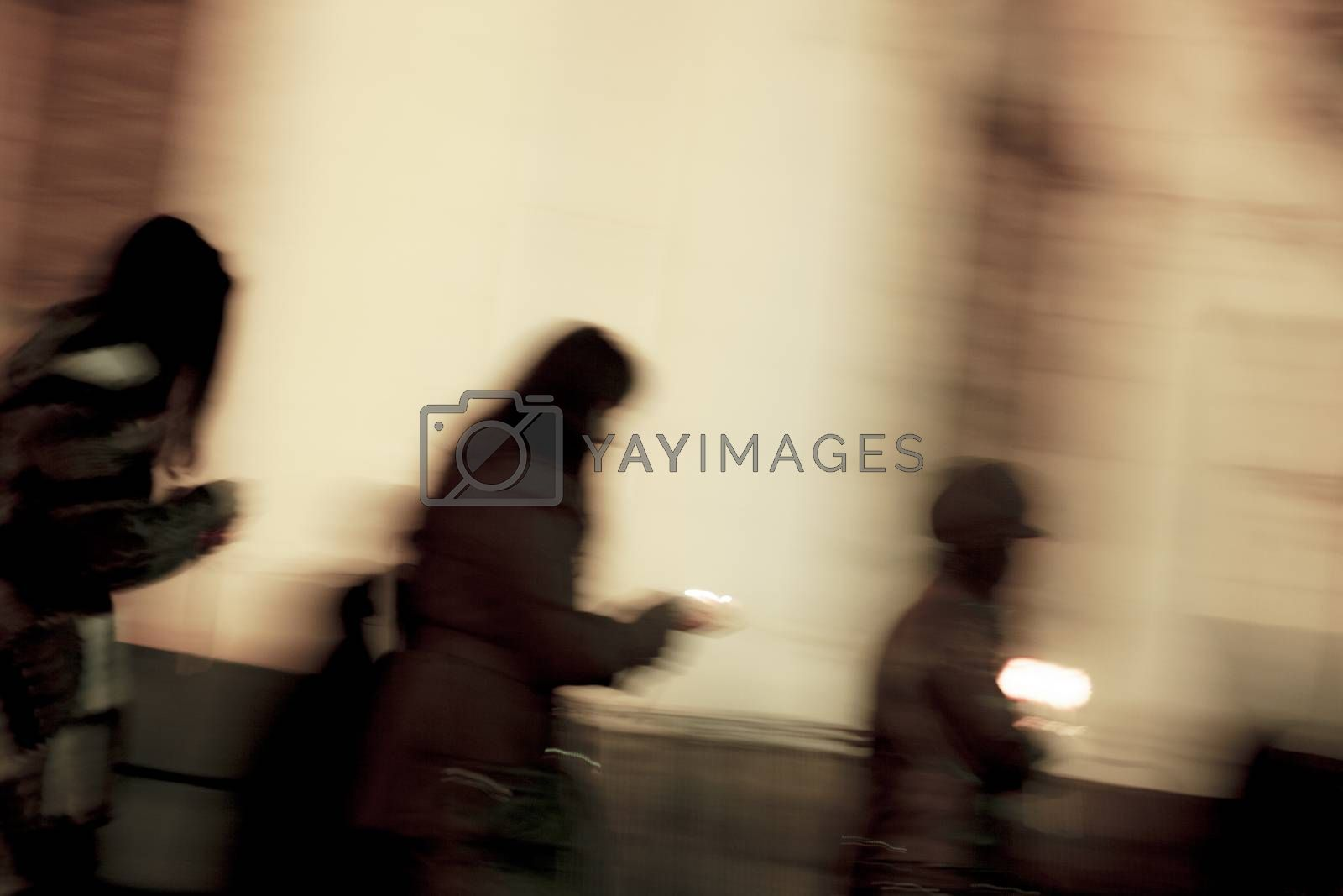 A blurred image of people with candles in their hands mourning or celebrating outdoors. Sepia colored. Night.