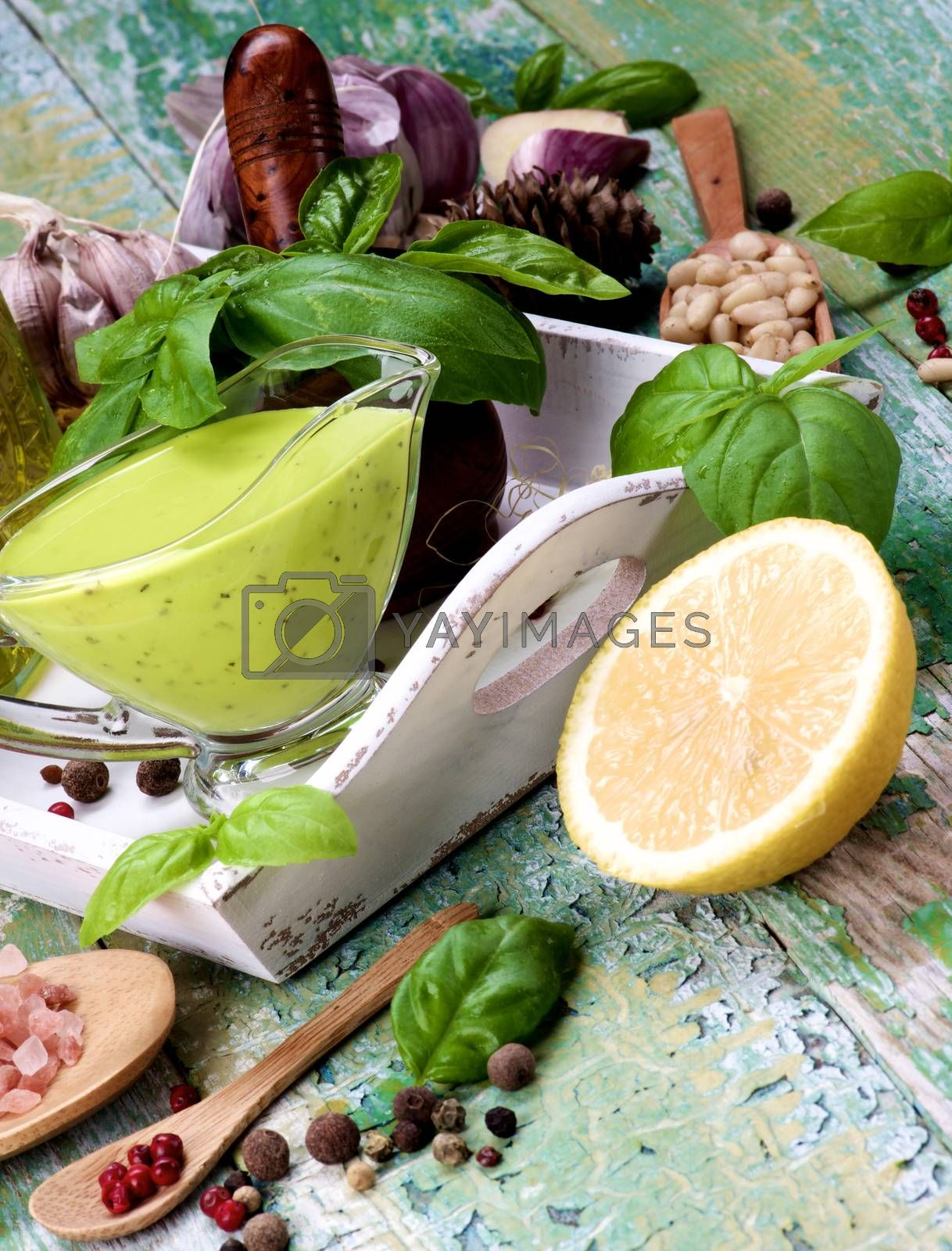 Arrangement of Homemade Freshly Made Creamy Pesto Sauce in Glass Gravy Boat with Ingredients in White Wooden Tray closeup Cracked Wooden background