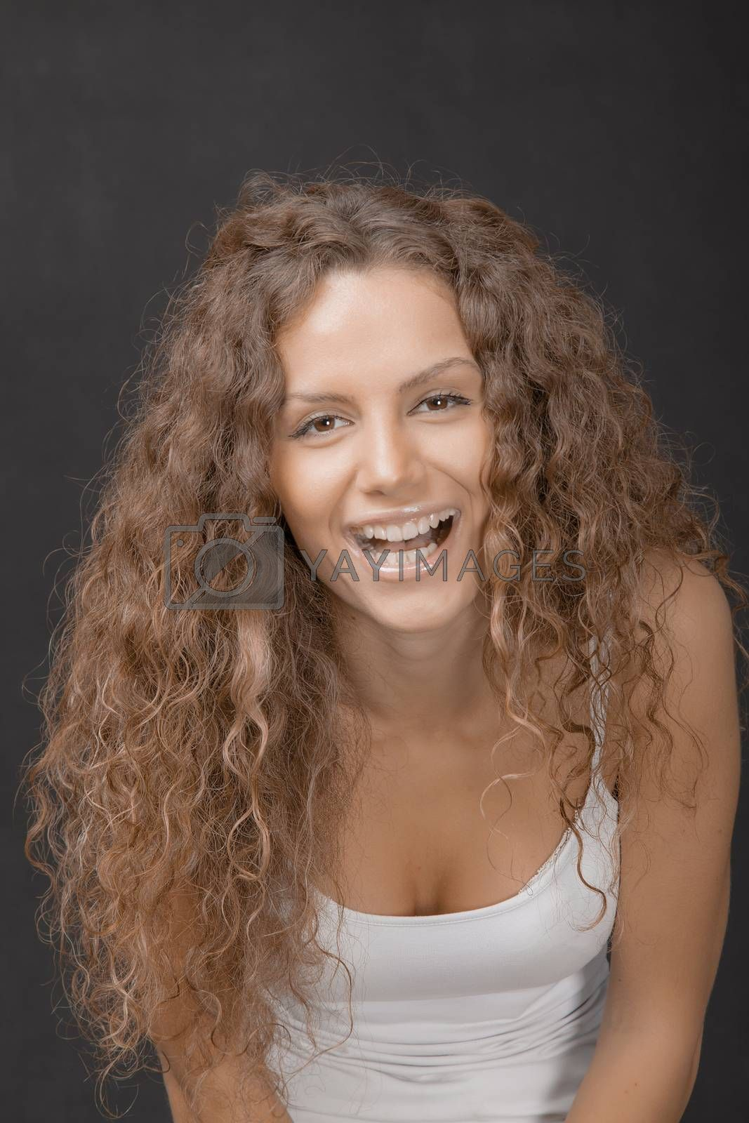 A young beautiful female with gorgeous hair laughing to camera. Studio shot.
