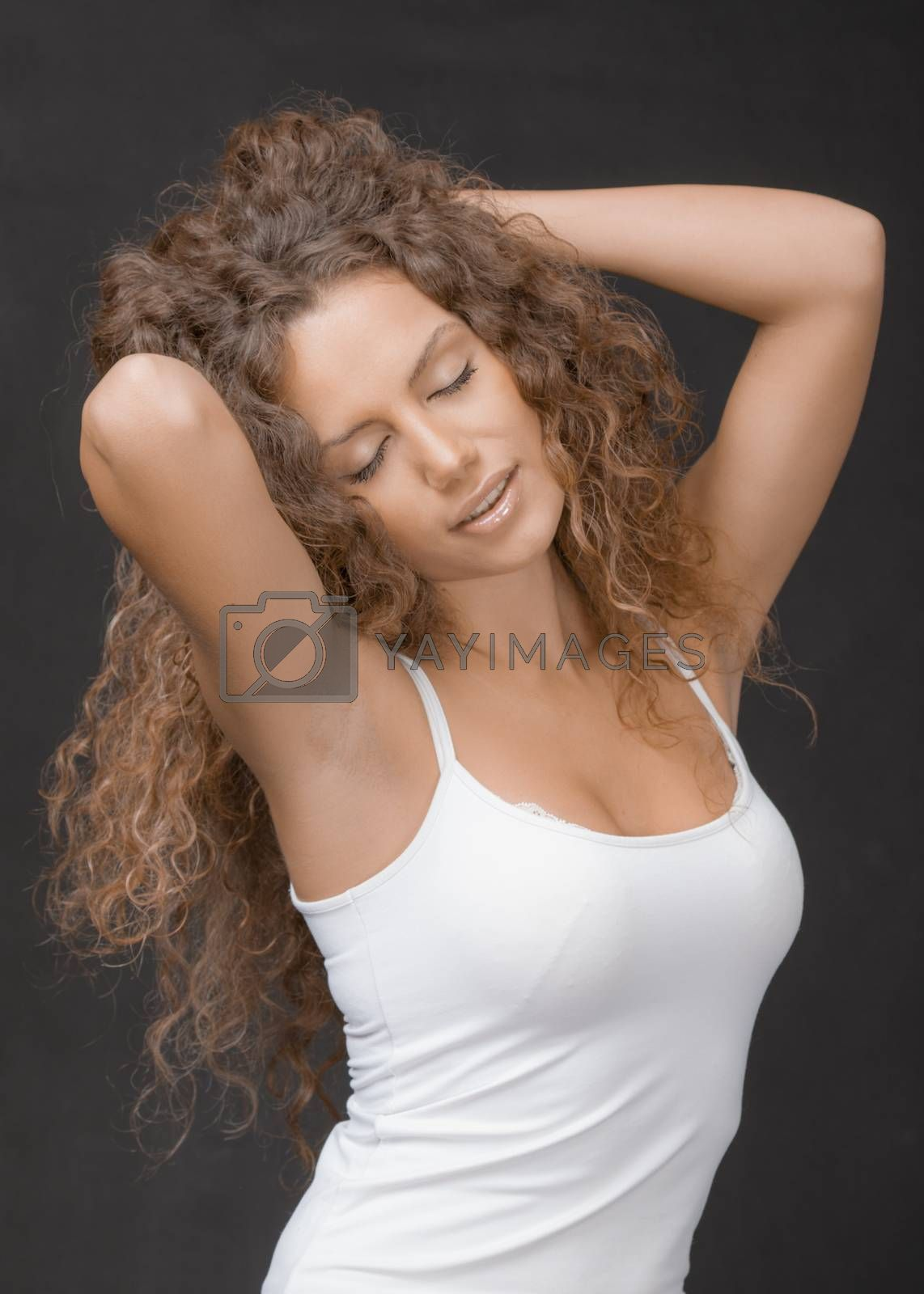 A portrait of a gorgeous woman with long curly hair, closed eyes, arms crossed behind neck stretching.
