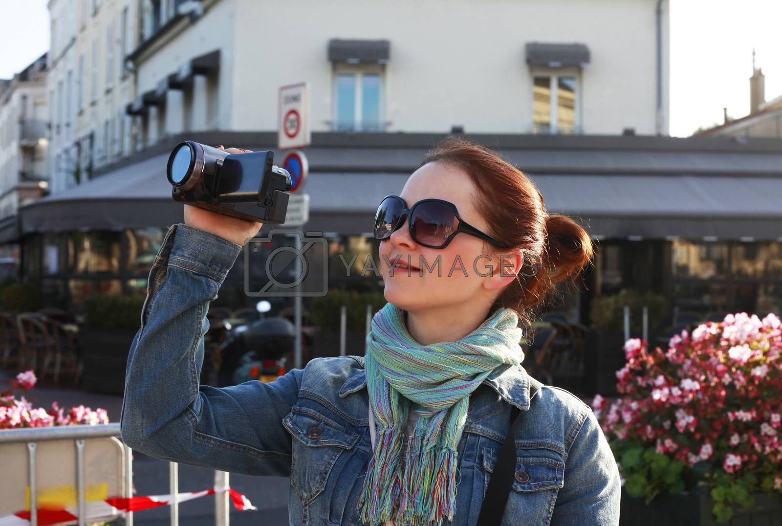 Girl using camcorder in the street Paris