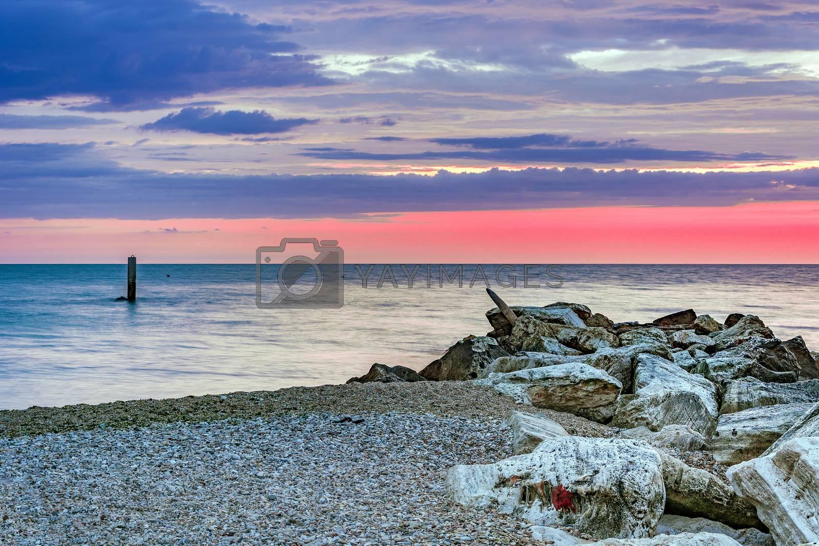 stony coastline with a cloudy  sunrise
