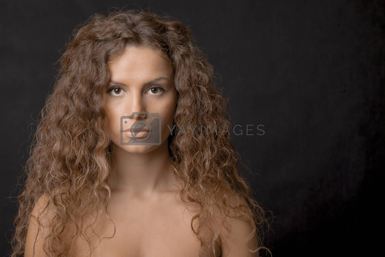 A beauty shot of a pretty young female with gorgeous curly long hair, low key.