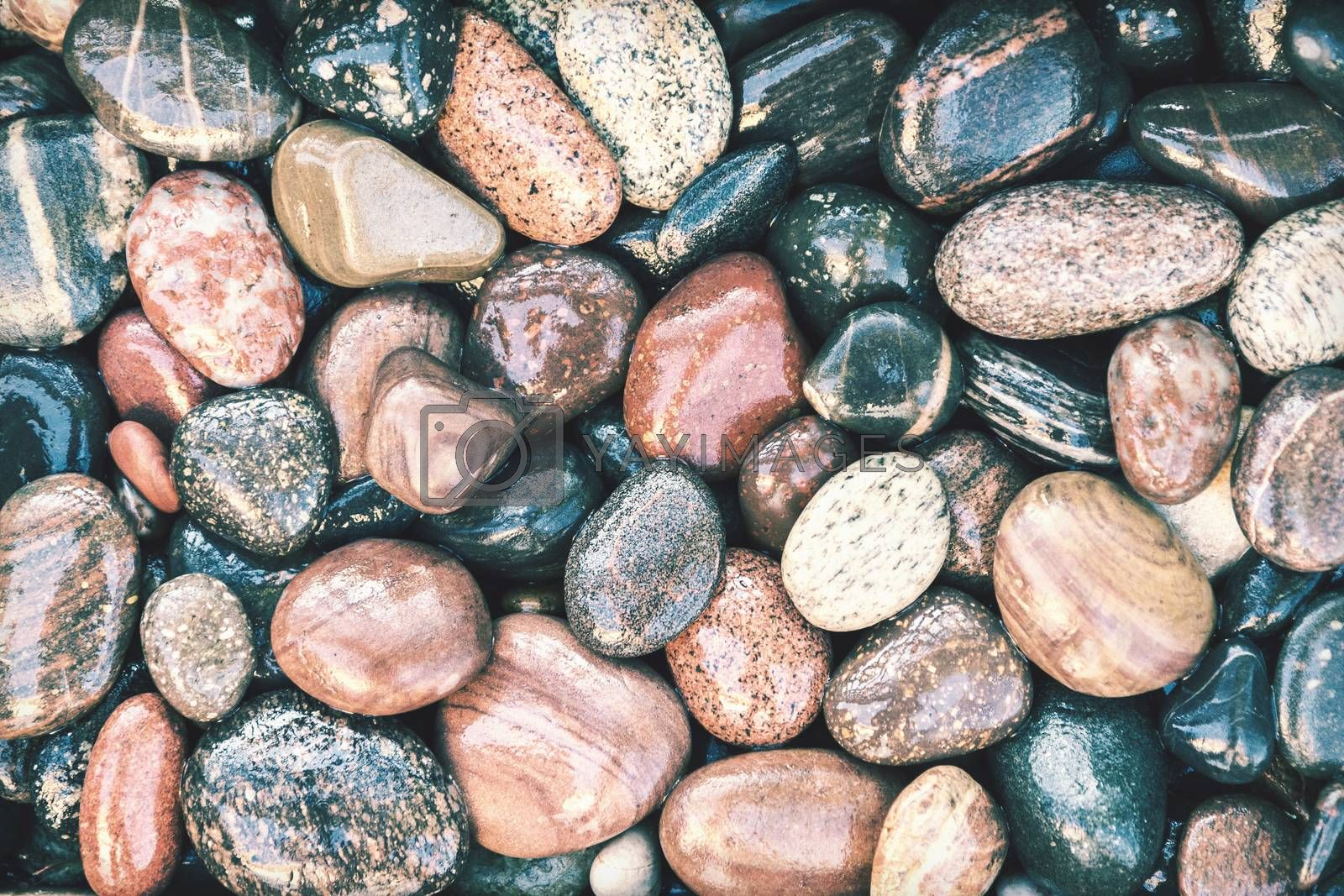Colorful wet pebbles background with retro faded photo effect