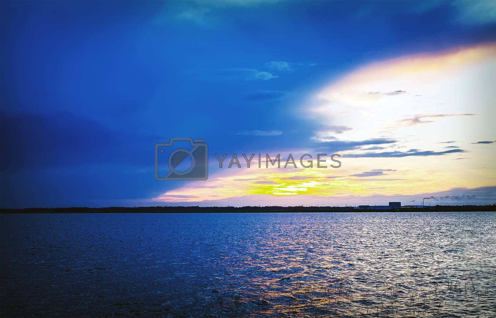 Bright blue and yellow sunset. The sun going beyond the horizon beyond the lake