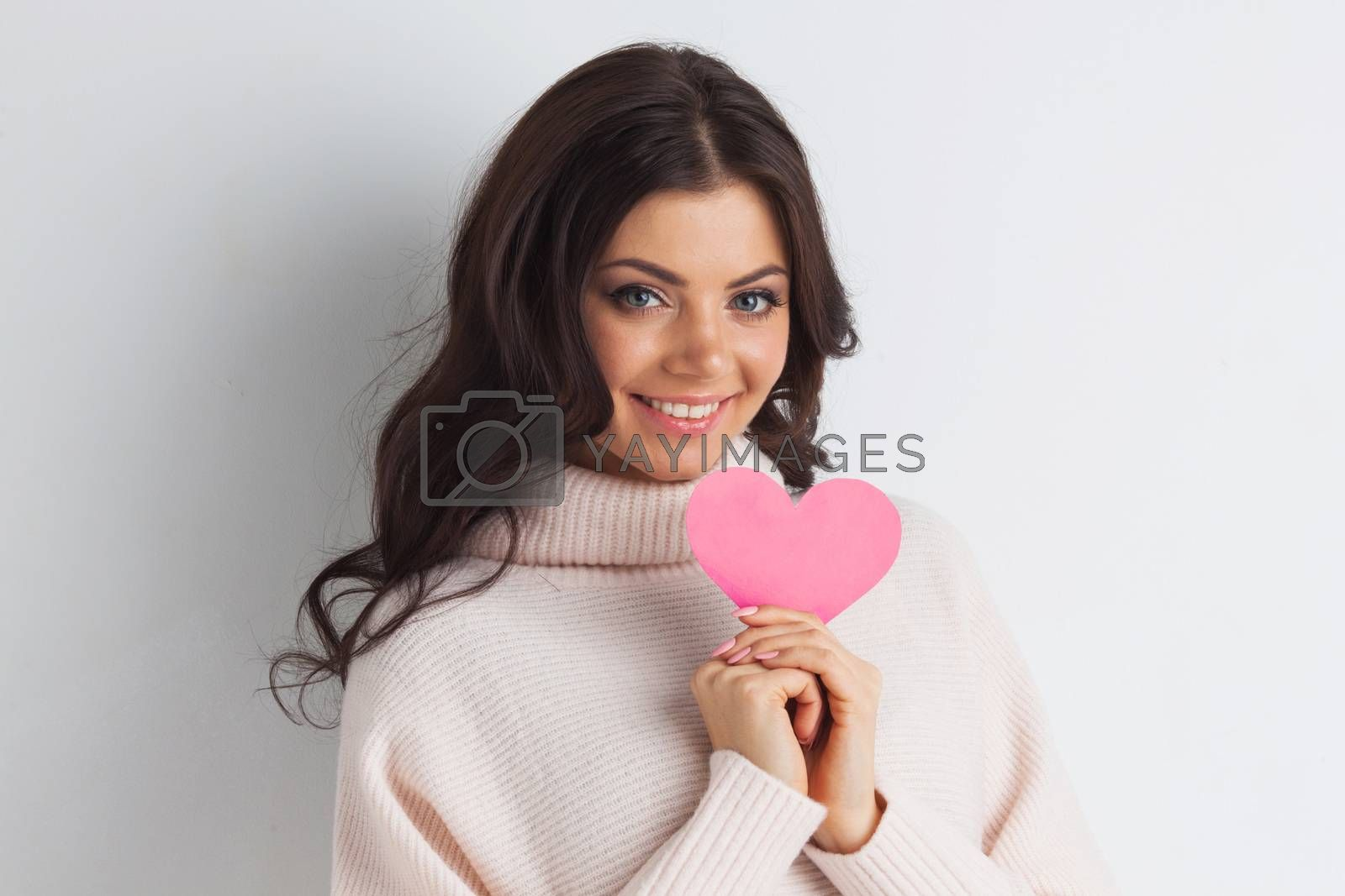 Beautiful young brunette woman holding pink paper heart, looking at camera