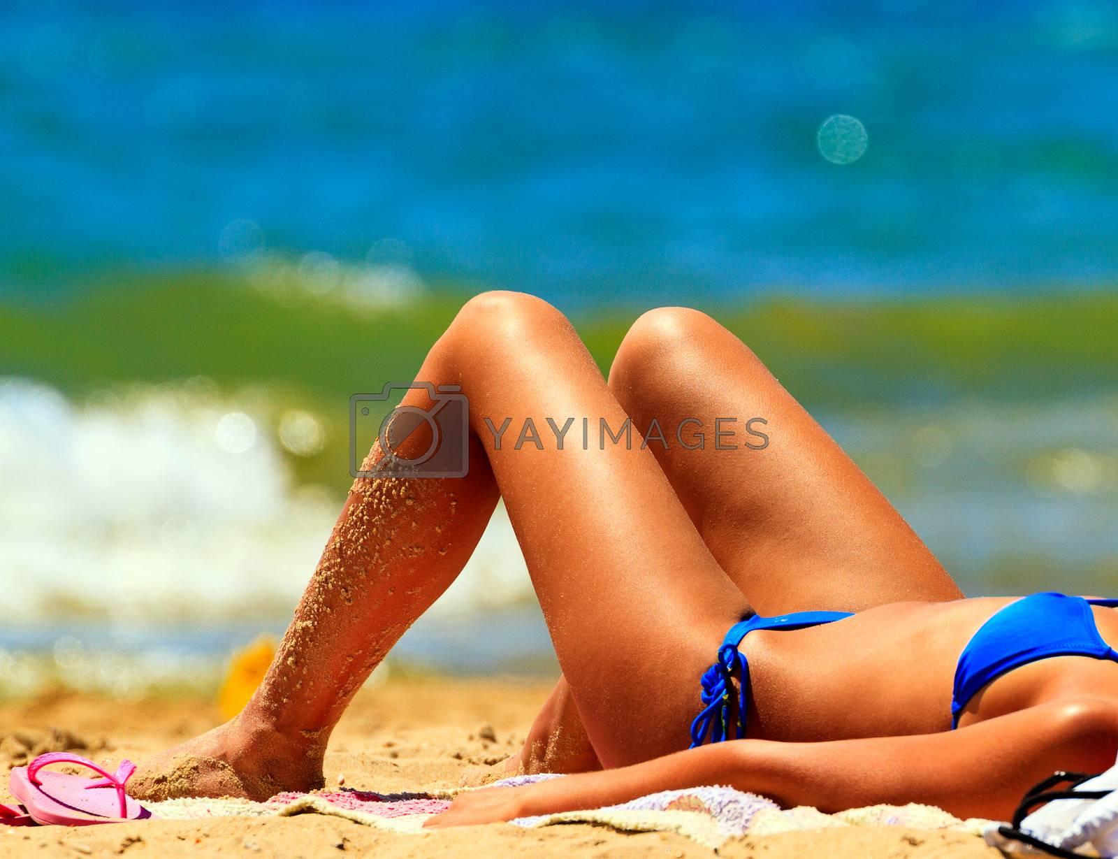 Woman sunbathing on a sandy beach