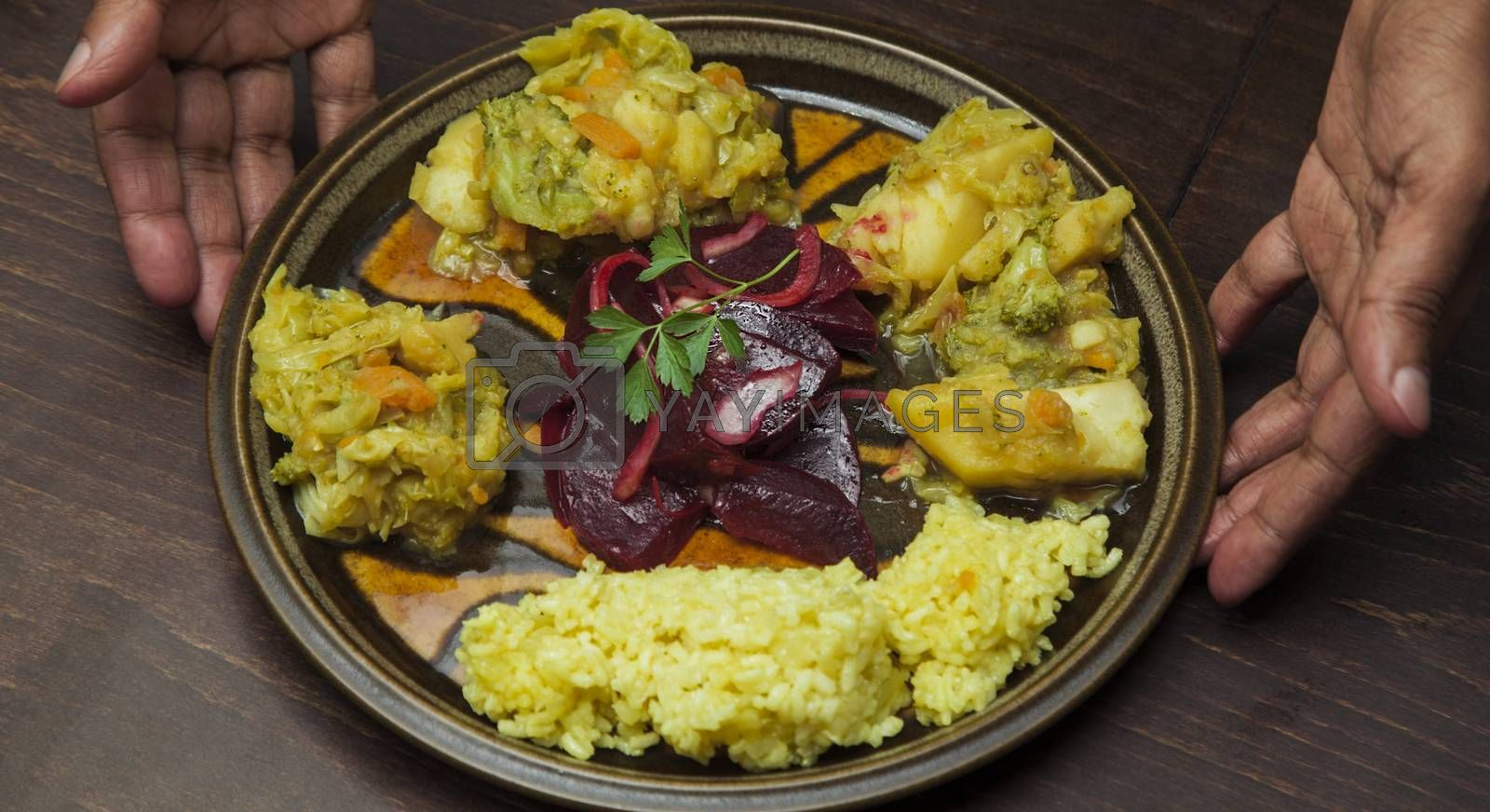 An afro-american man s hands are presenting a plate with vegetable stew and salad of red beetroot.