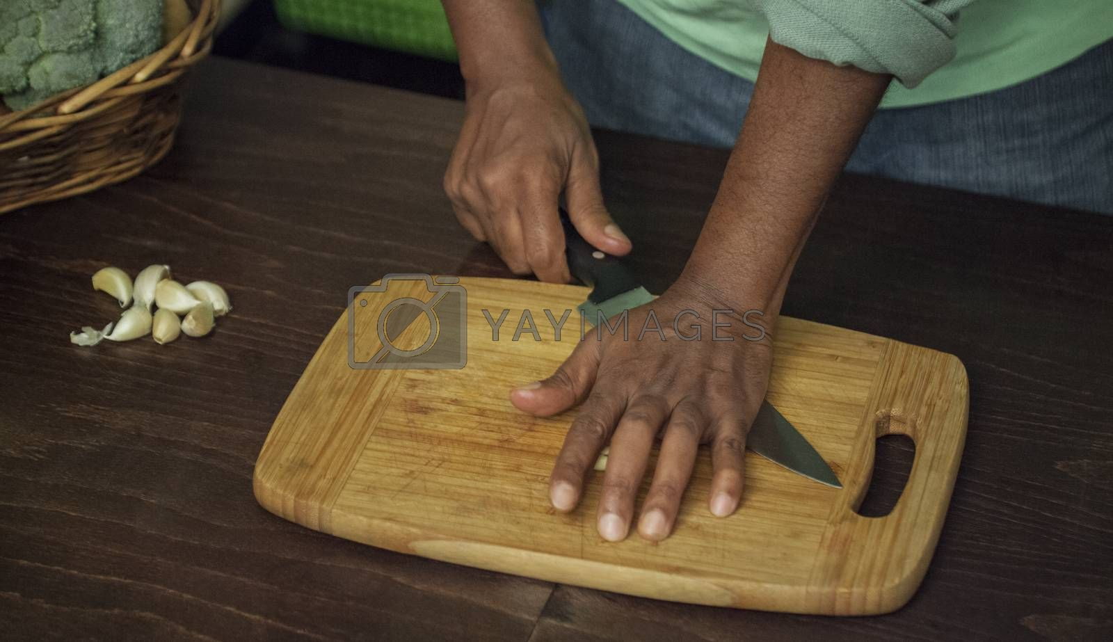 An afro-american man s hand is pressing with a knife garlic on a wooden board.