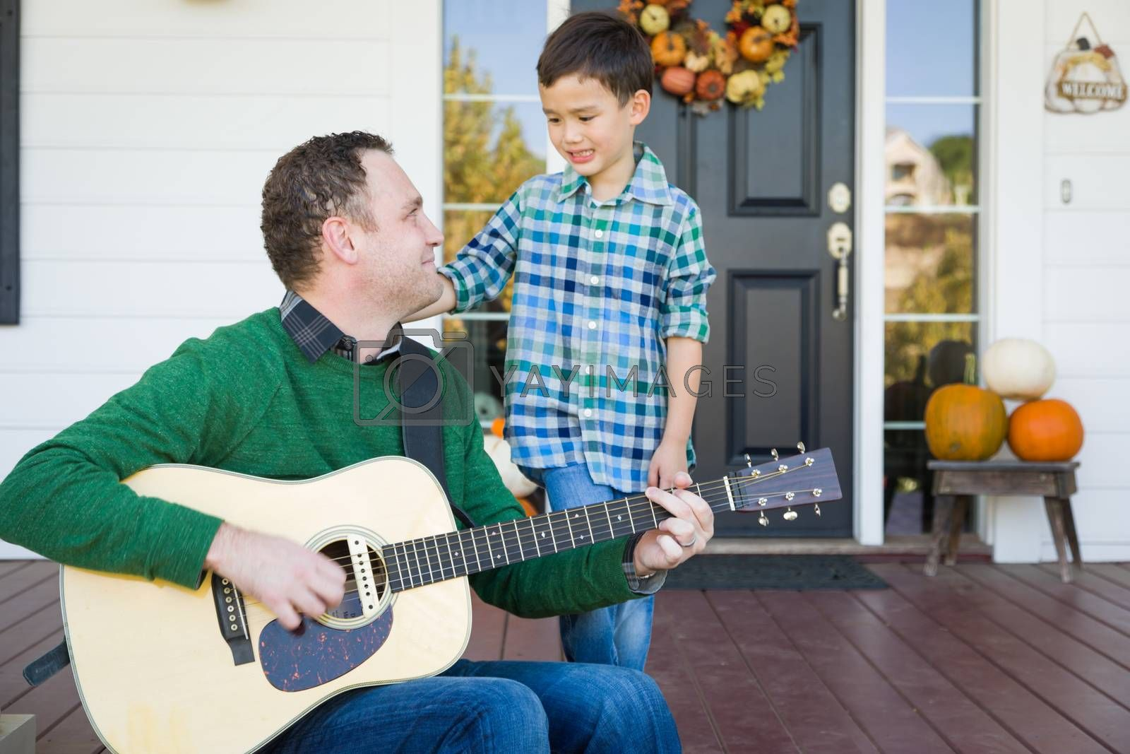 Young Mixed Race Chinese and Caucasian Son Singing Songs and Playing Guitar with Father by Feverpitched