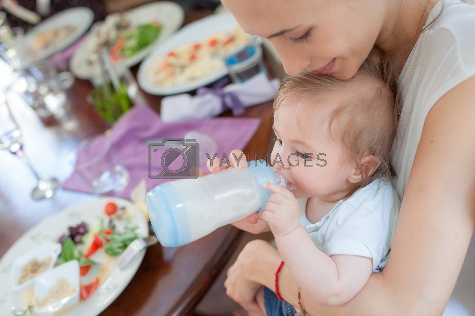 Young beautiful mother is feeding her cute  little boy with milk in a restaurant.