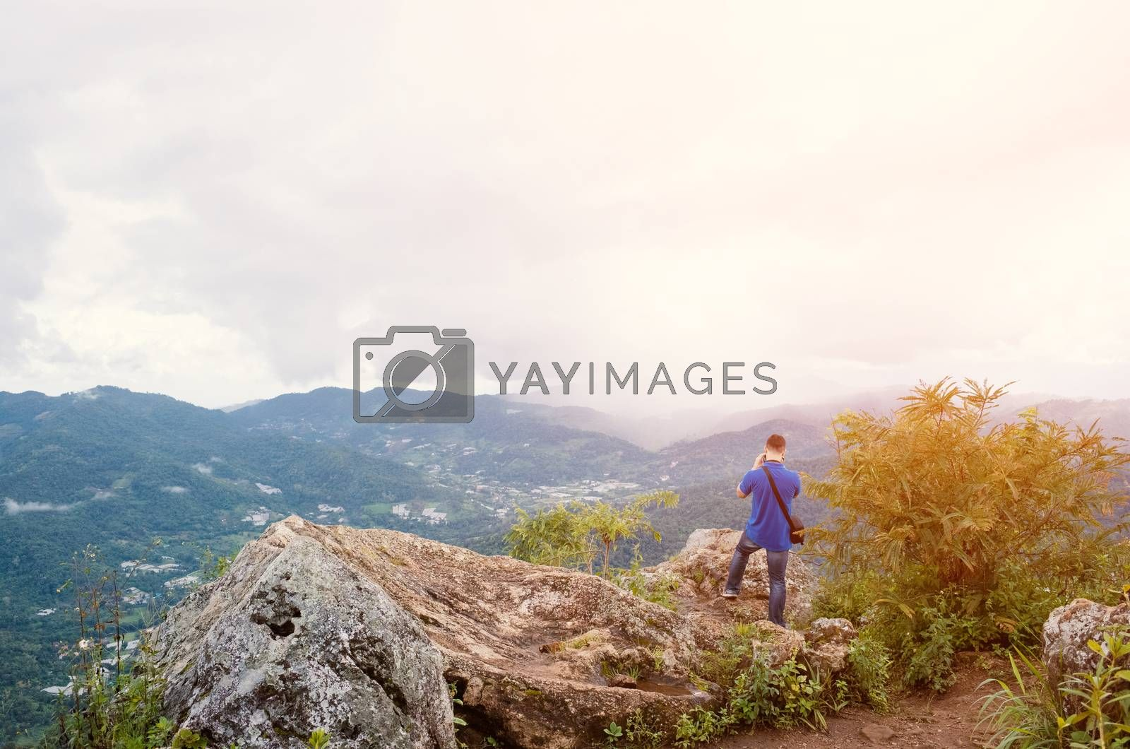 Young traveler standing on the mountains looks into the sunset.