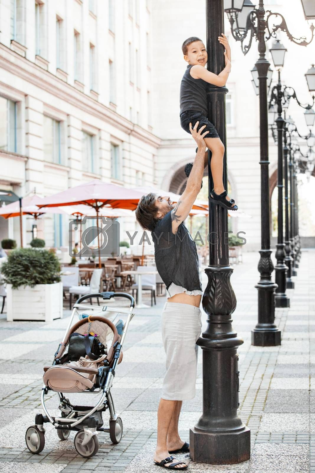 A handsome father is holding up his young boy on a street pillar.