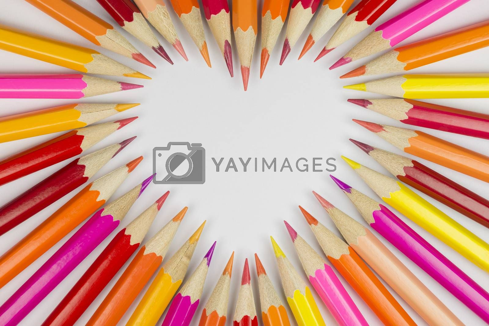 Collection of colored pencils in heart shape in top view as background picture