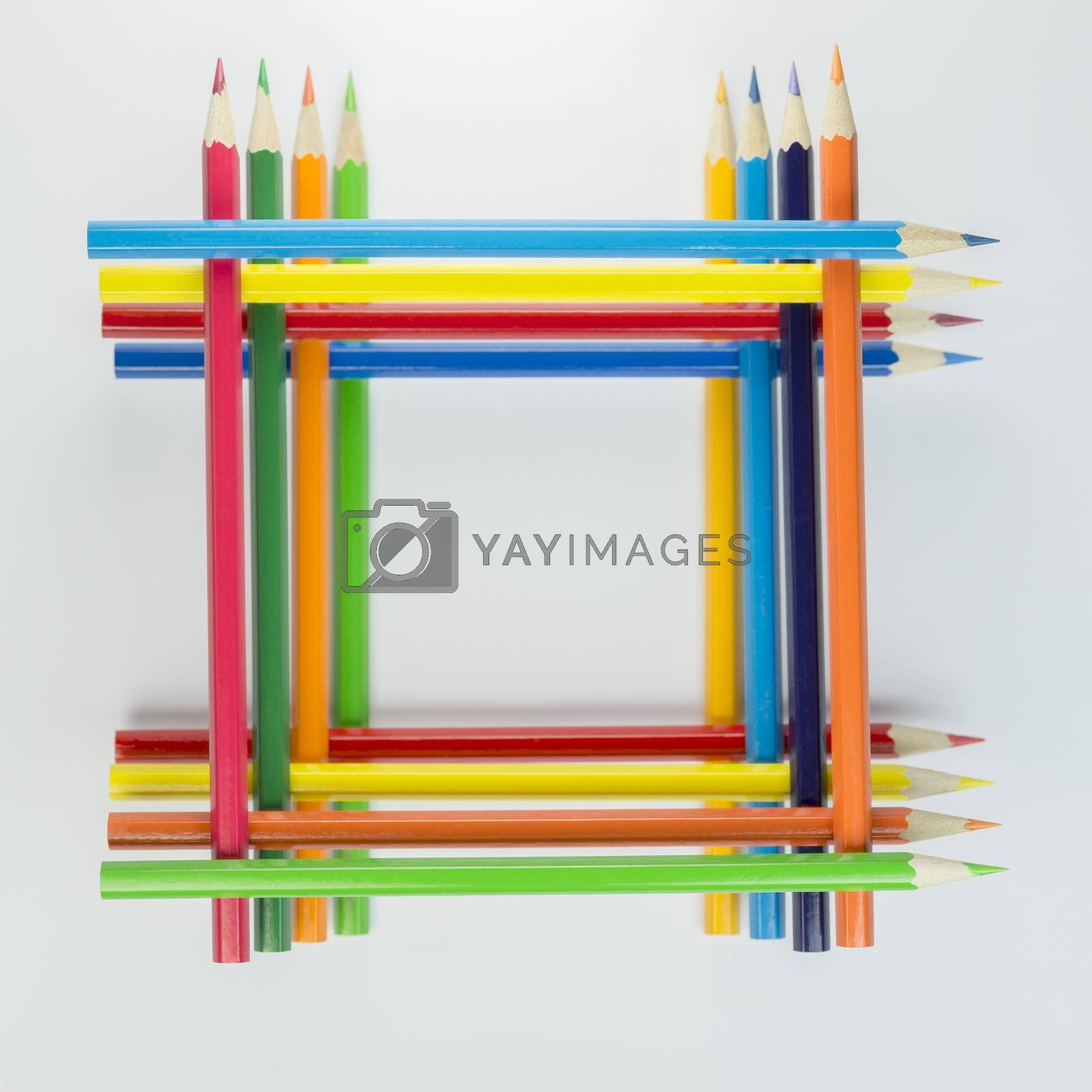 Collection of stacked colored pencils in a square in top view as background picture