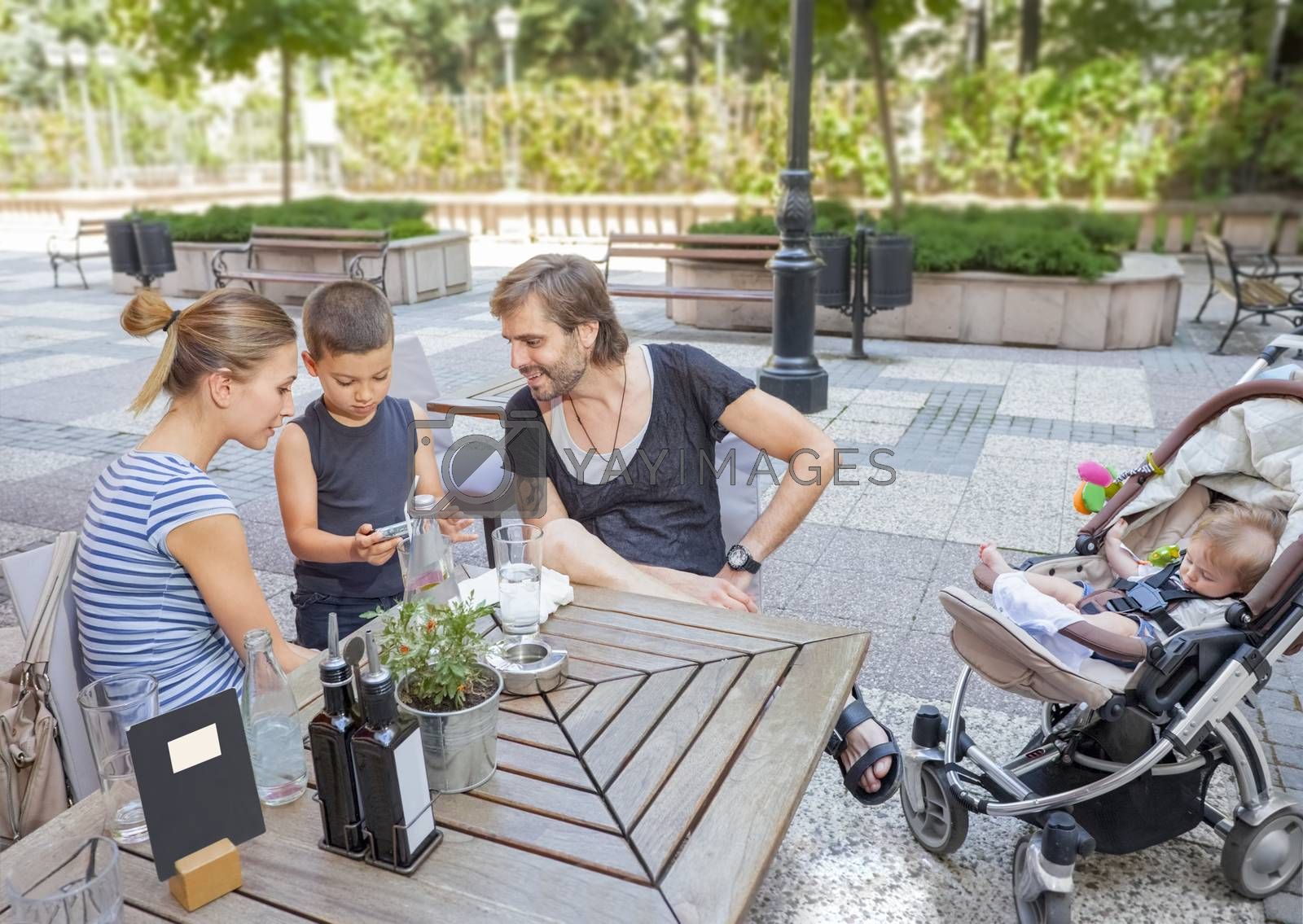 A young couple with their two children - a boy and a baby relaxing in a nice cafe outdoors in summer.